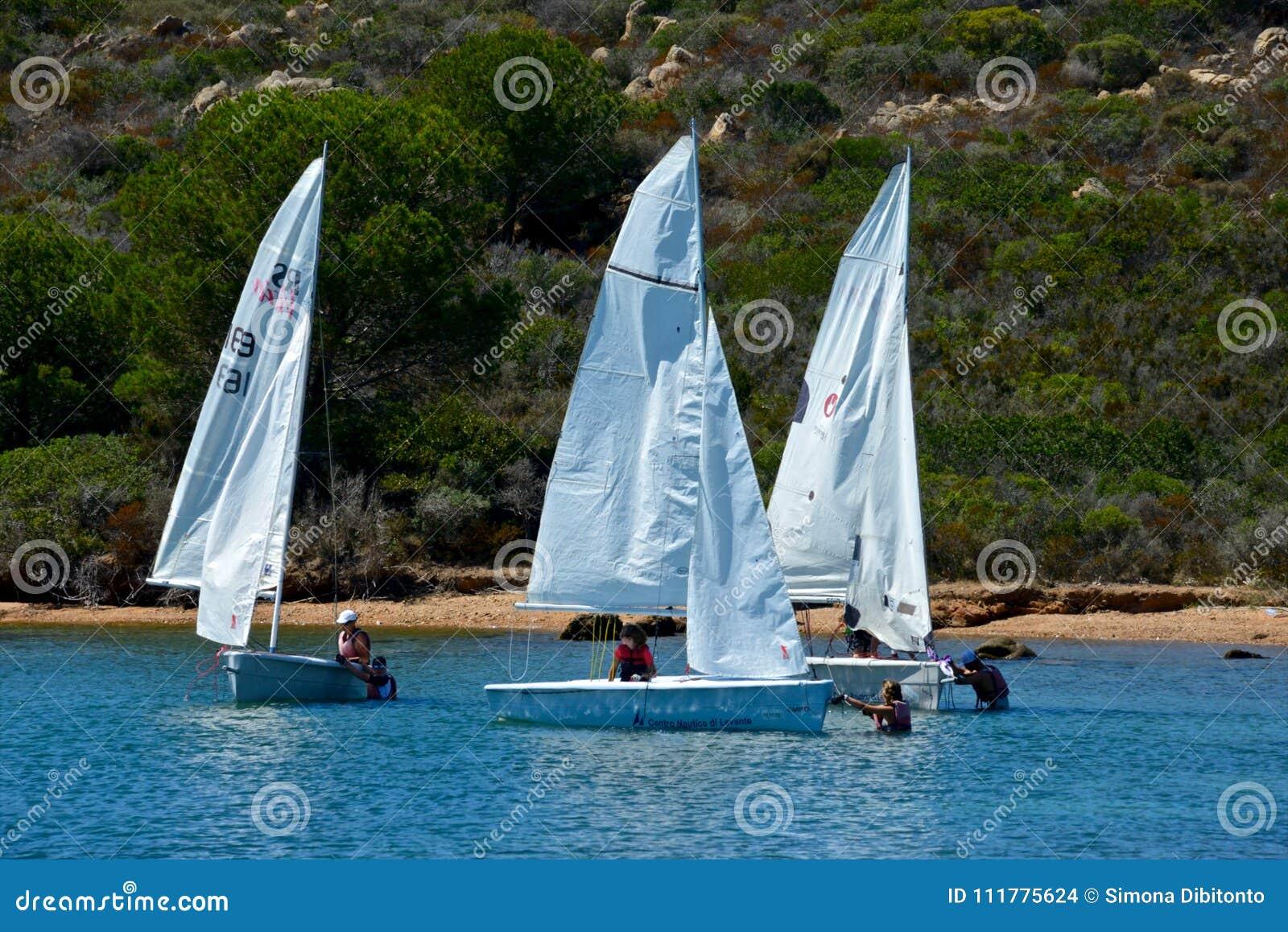 Белые парусники при люди уча плавать в голубом море окруженном по своей природе