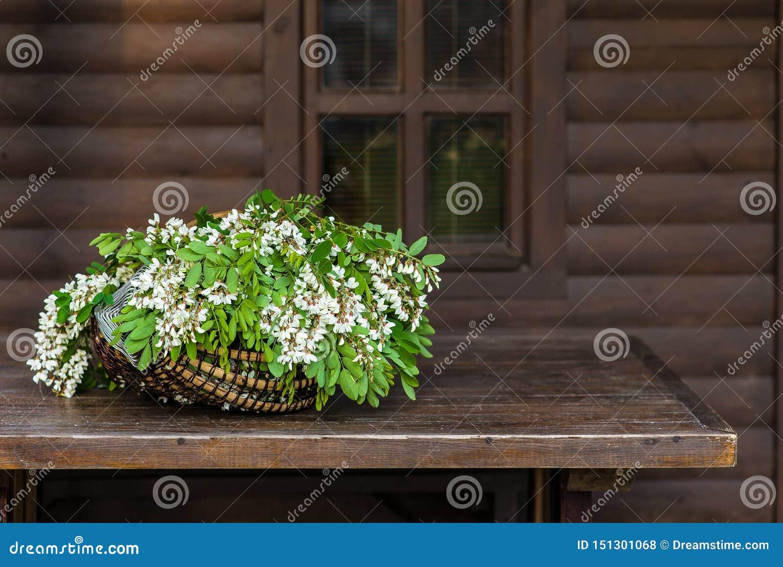 Белые цветки акации с листьями лежат в плетеной корзине