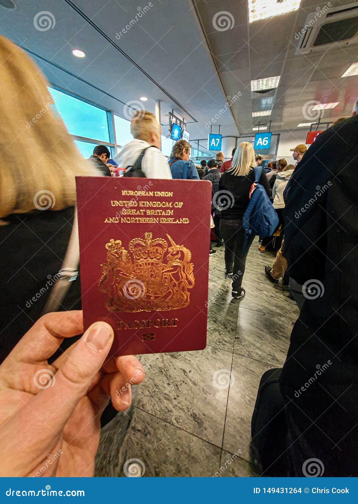 Белый мужчина держит его красный великобританский паспорт в его руке в середине толпить терминала отклонения