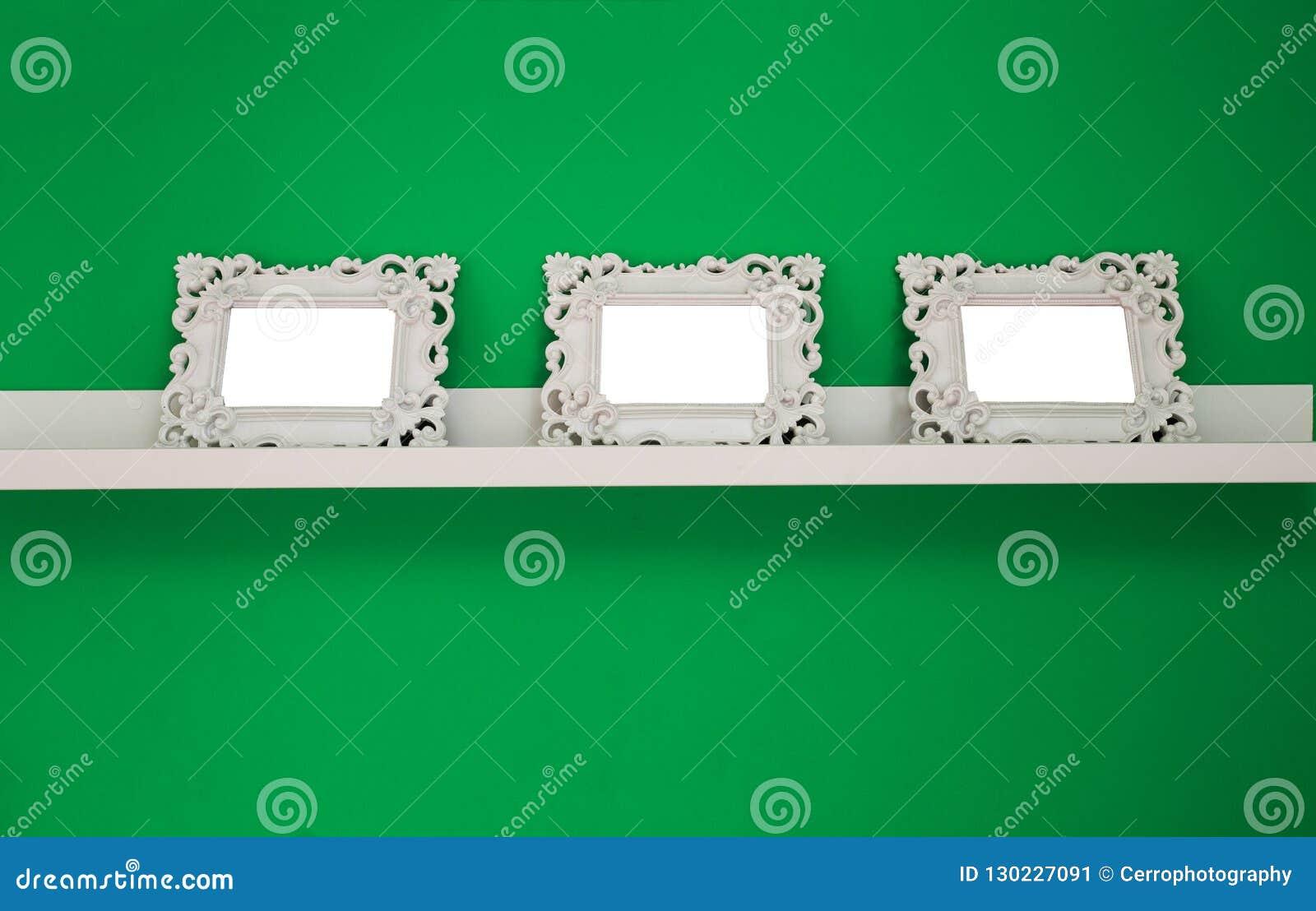 3 белых пустых рамки фото на зеленой стене и деревянной полке, космос для текста или фото