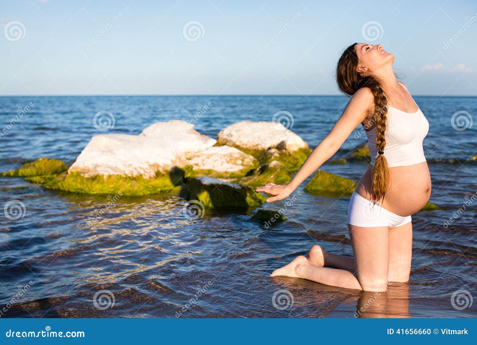 Беременная женщина в бюстгальтере спортов делая тренировку в релаксации на представлении йоги на море