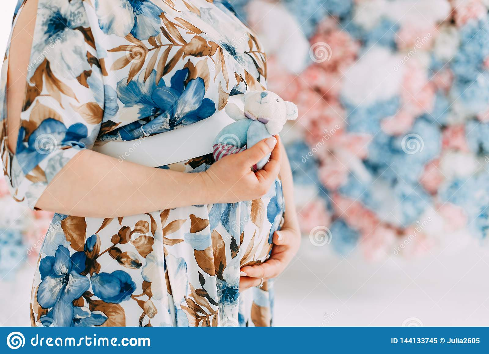 Беременная женщина в чувствительном голубом платье штрихуя ее живот