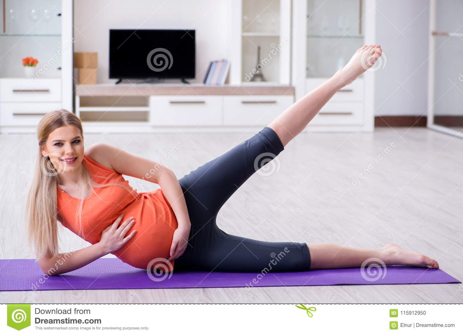 Беременная женщина делая тренировку спорта дома