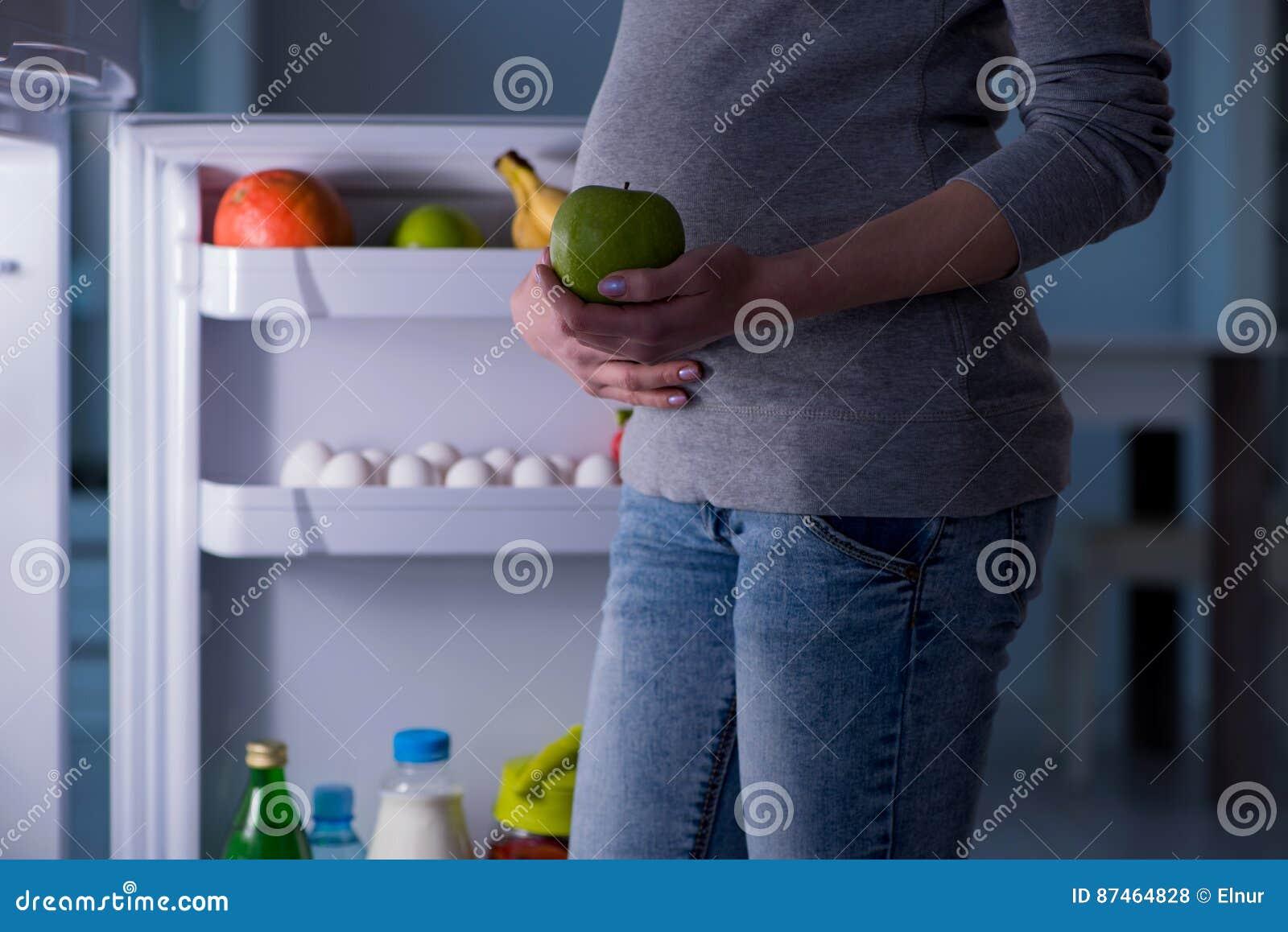 Беременная женщина около холодильника ища еда и закуски на ноче