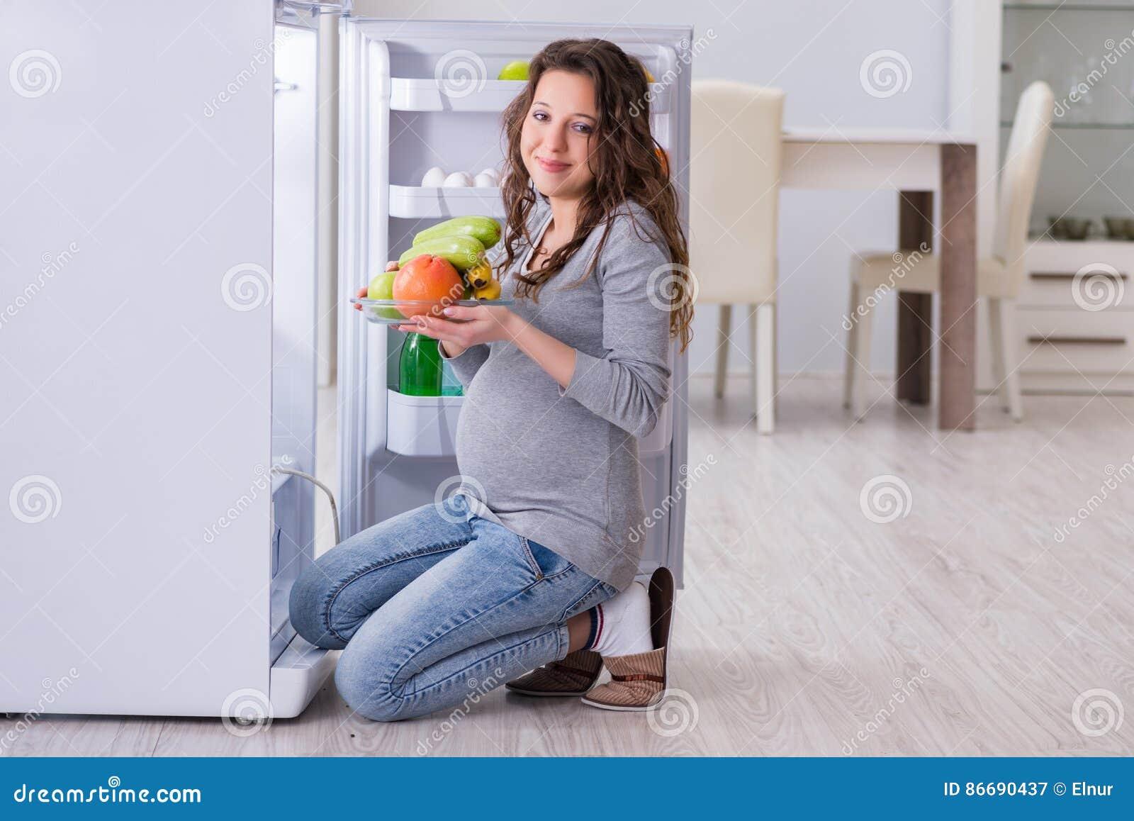 Беременная женщина около холодильника ища еда и закуски