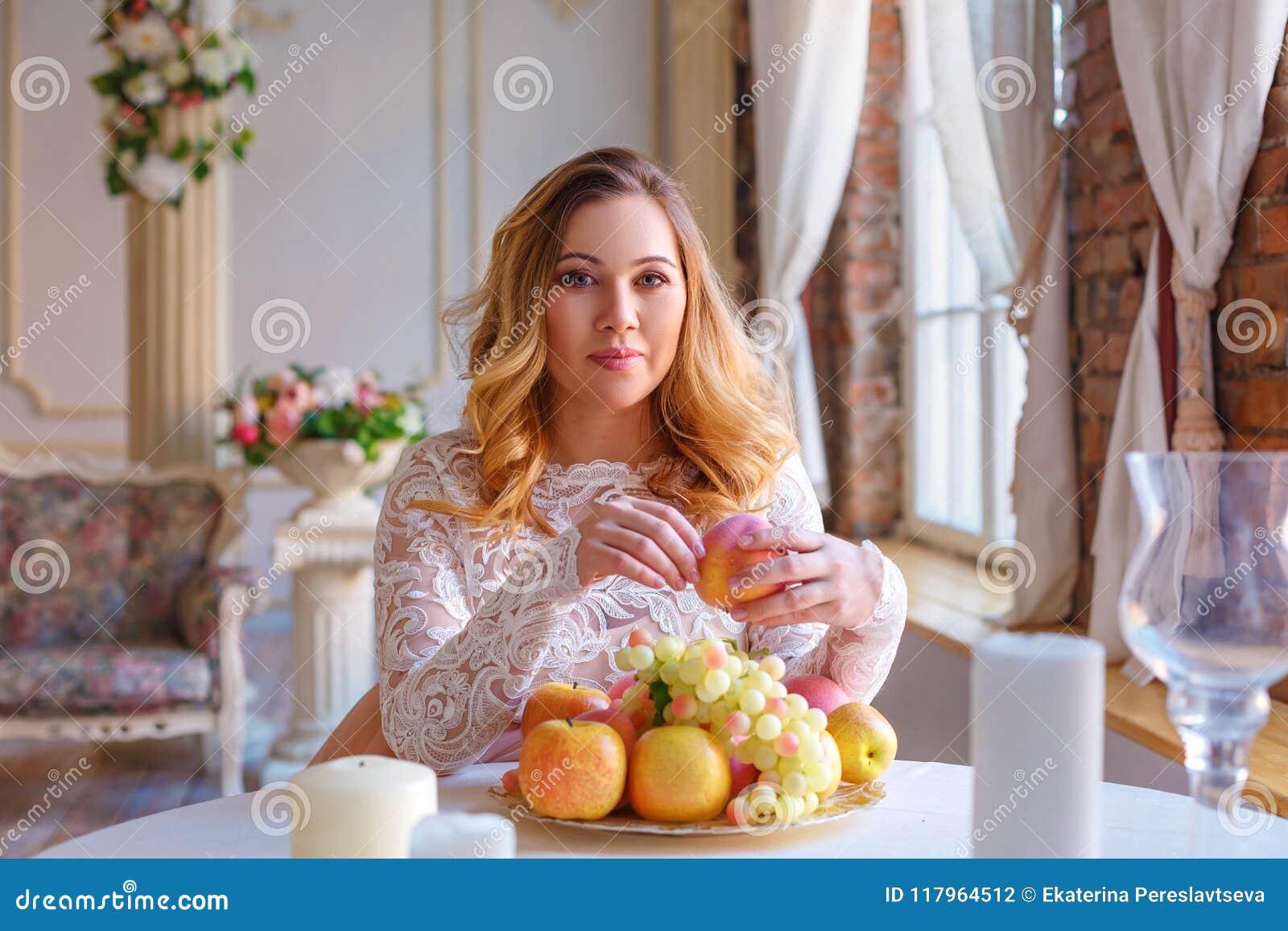 Беременная женщина сидя на таблице в красивом платье, концепции материнства