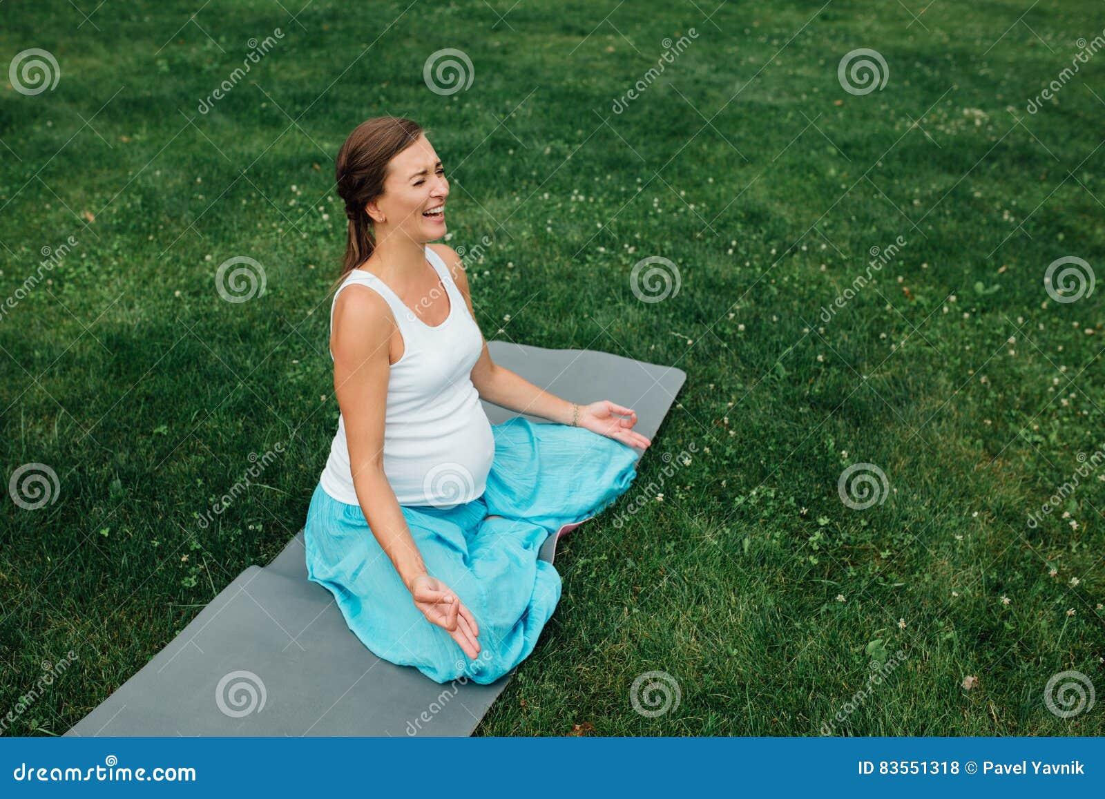 Беременная йога в положении лотоса на предпосылке леса в парке циновка травы, внешняя, женщина здоровья