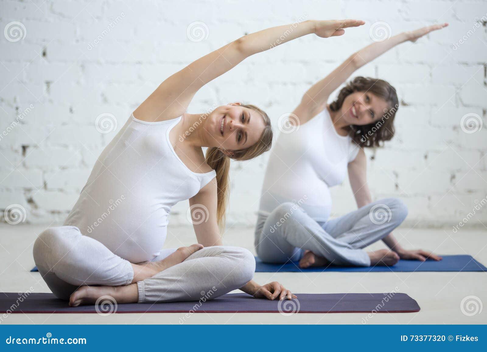 Беременные молодые женщины делая пренатальную йогу Гнуть в легком представлении