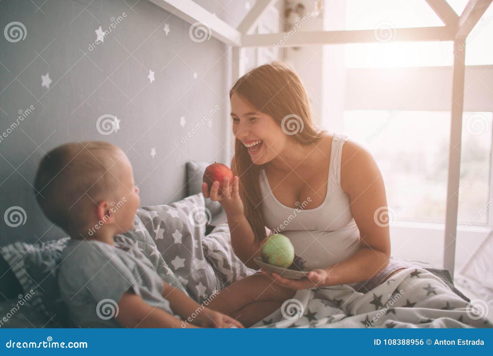 Беременный сын матери и мальчика ест яблоко и персик в доме кровати t в утре Вскользь образ жизни внутри