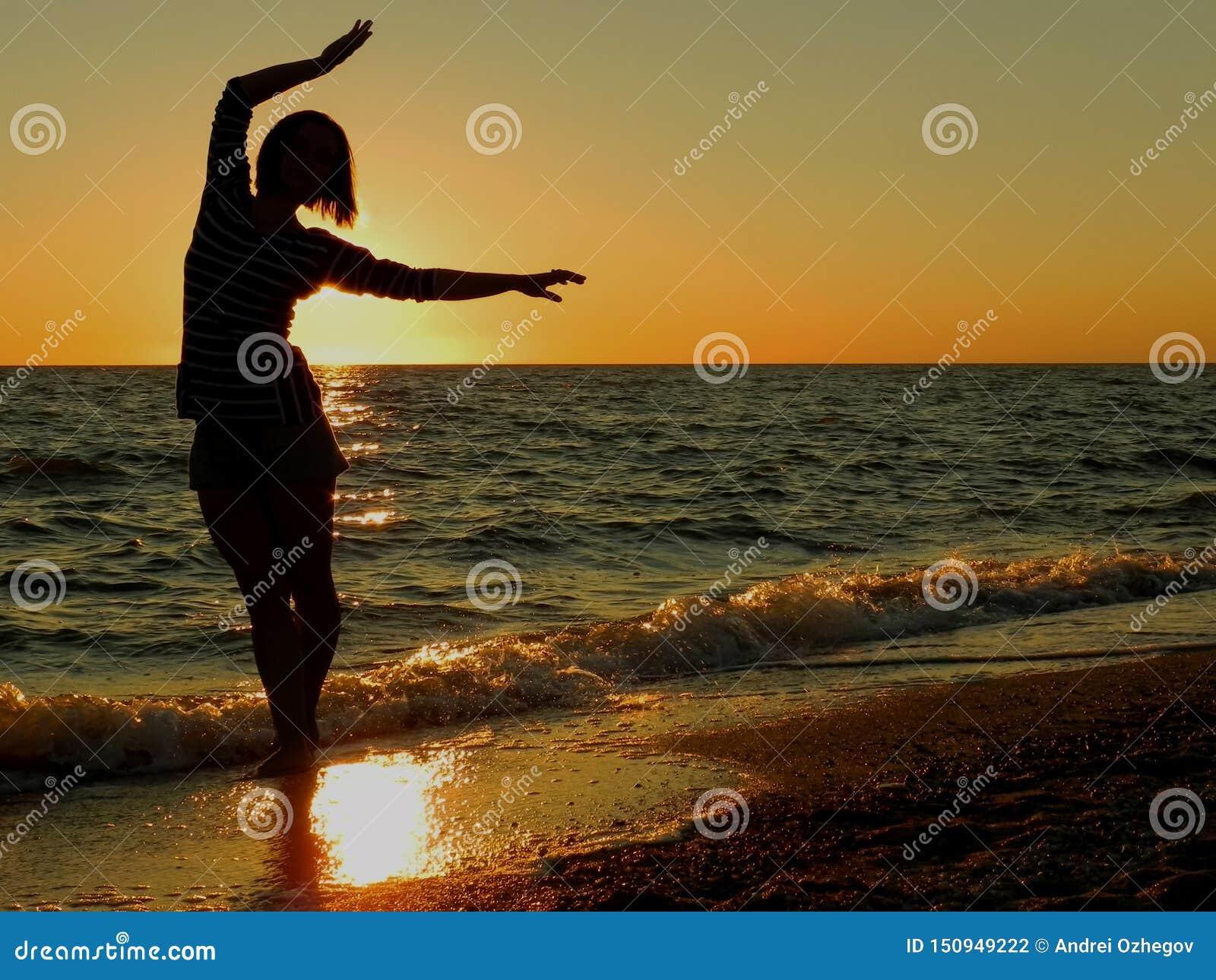 Беспечальные танцы женщины в заходе солнца на пляже