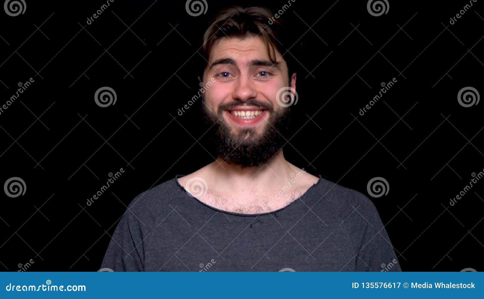Беспечальный радостный красивый человек с бородой имея сияющие глаза раскрывая его рот с утехой разрывая в смеяться положительно