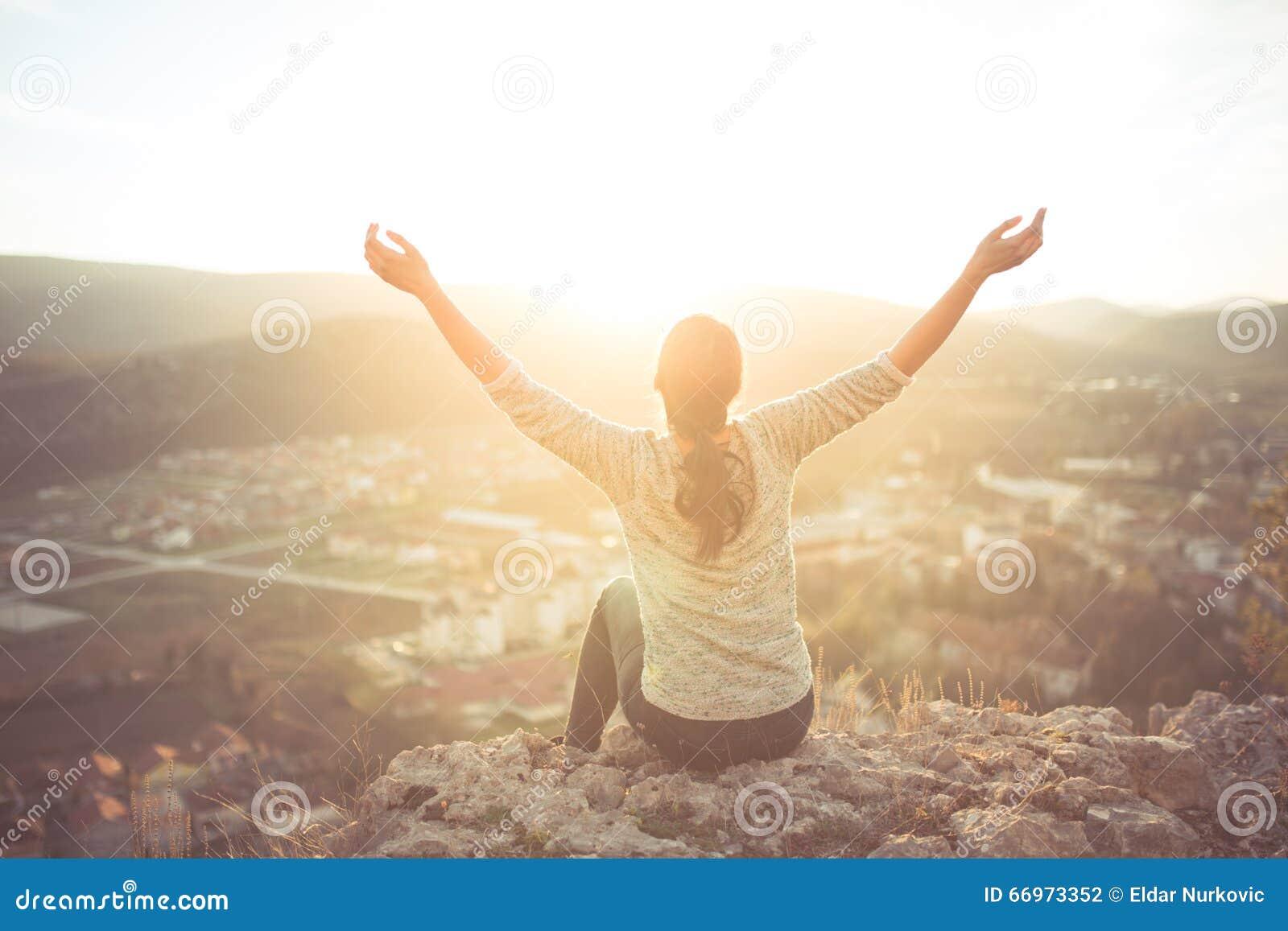 Беспечальная счастливая женщина сидя na górze скалы края горы наслаждаясь солнцем на ее руках повышения стороны в солнечном свете