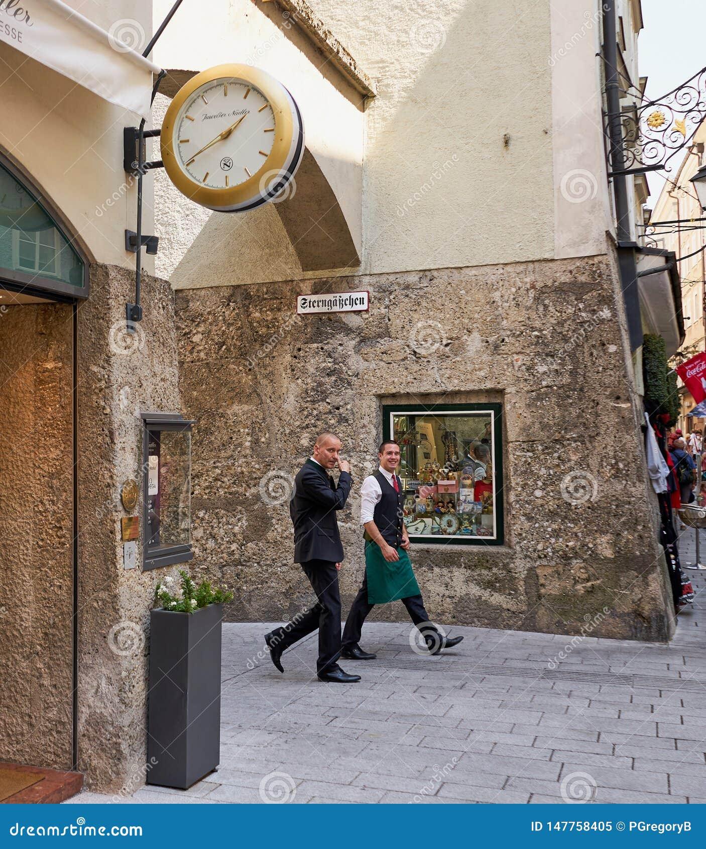 Беспристрастная съемка 2 бизнесменов идя в Зальцбург, Австрию