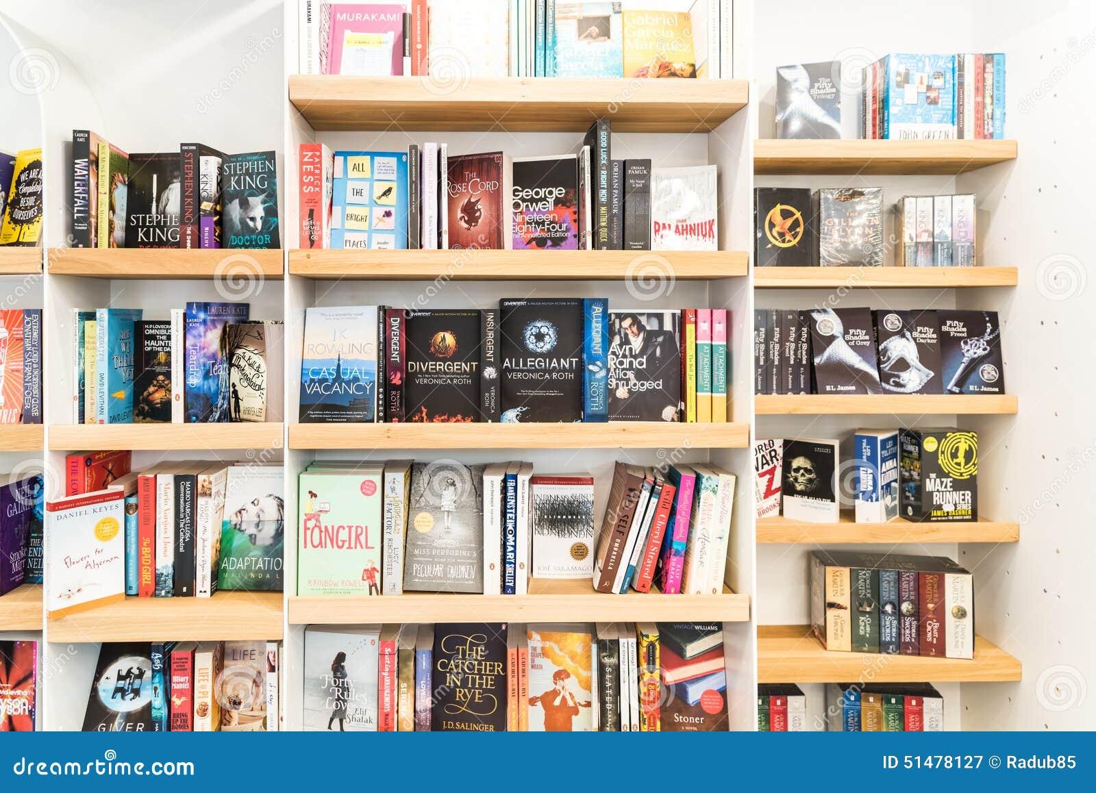Бестселлер записывает для продажи на полке библиотеки