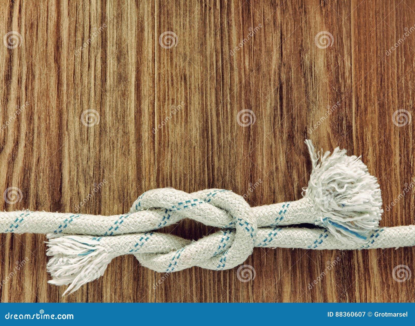 Белая веревочка с морским узлом рифа на предпосылке w grunge деревянной