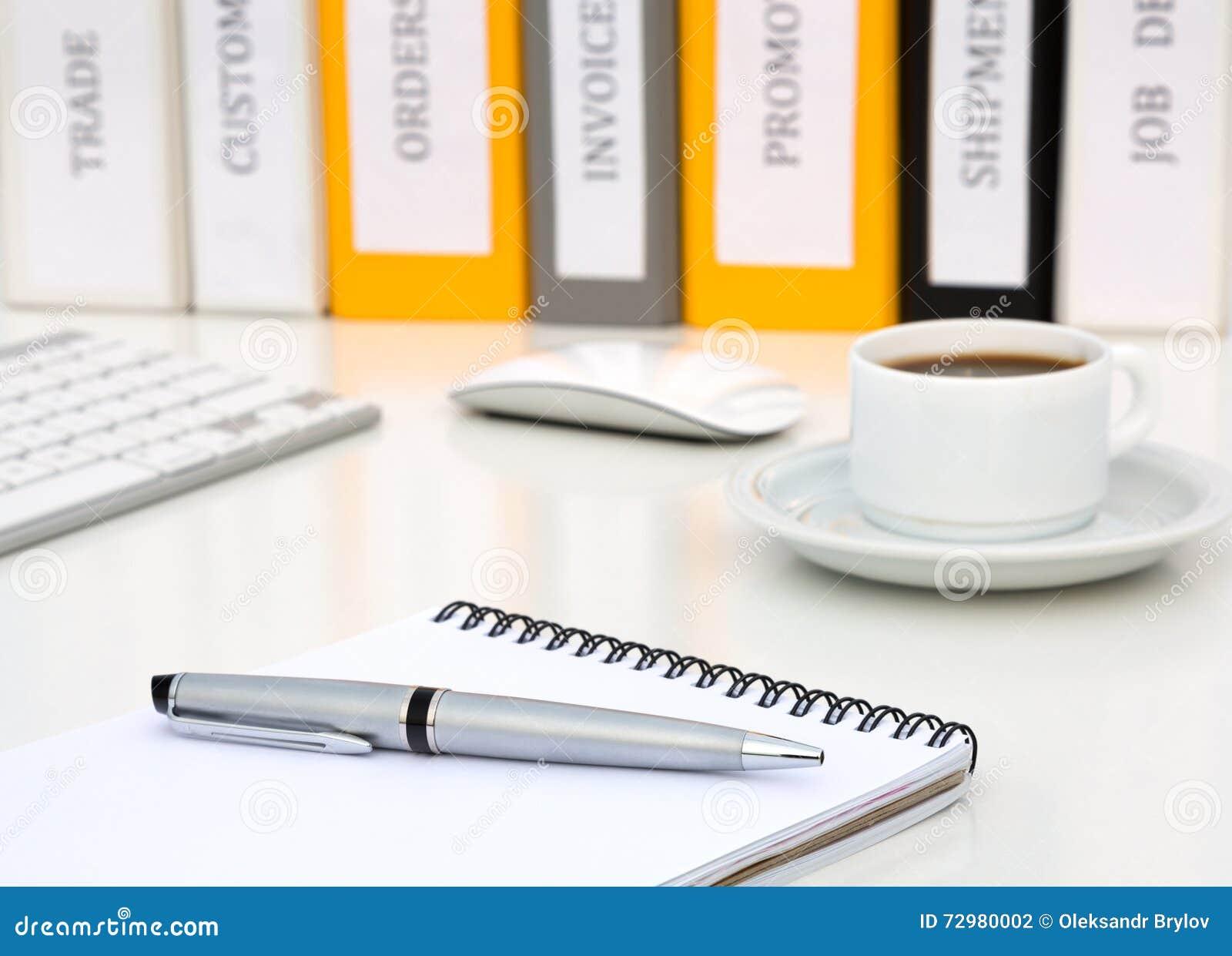 Белая таблица офиса с компьютером кофе ручки металла исполнительного класса блокнота серым