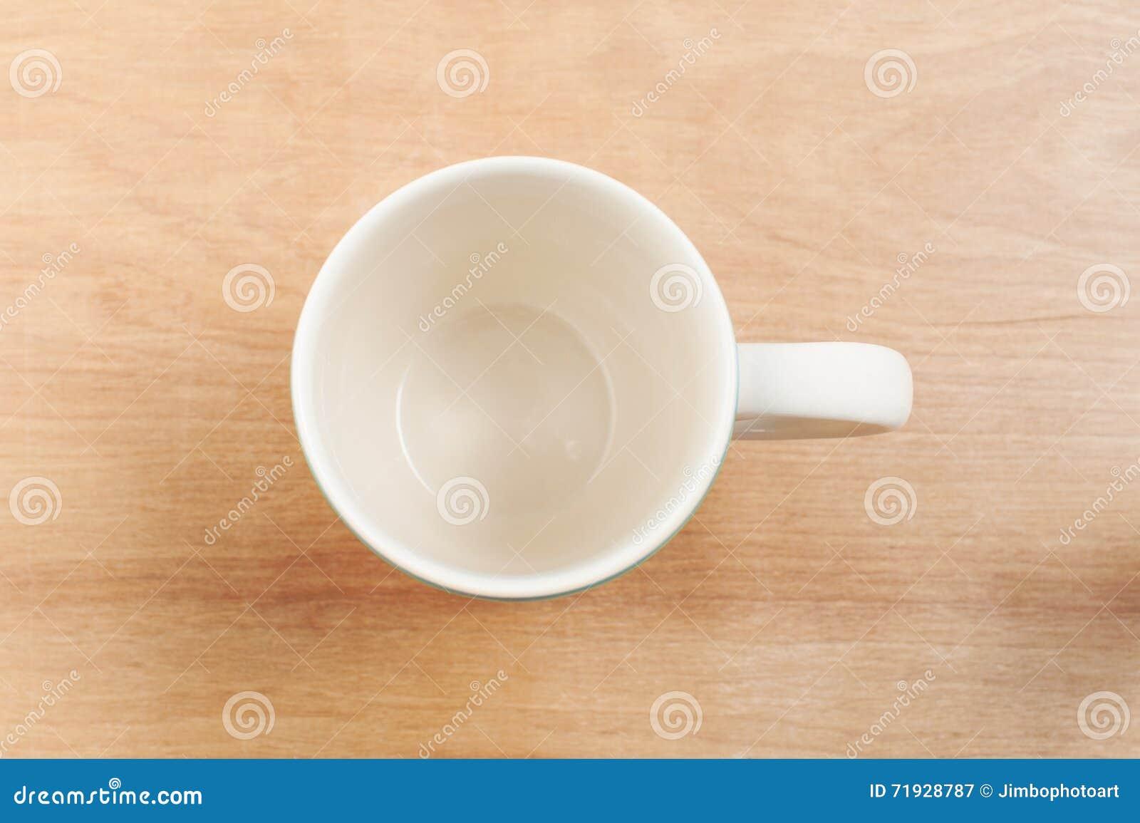 Белое взгляд сверху чашки на деревянном столе