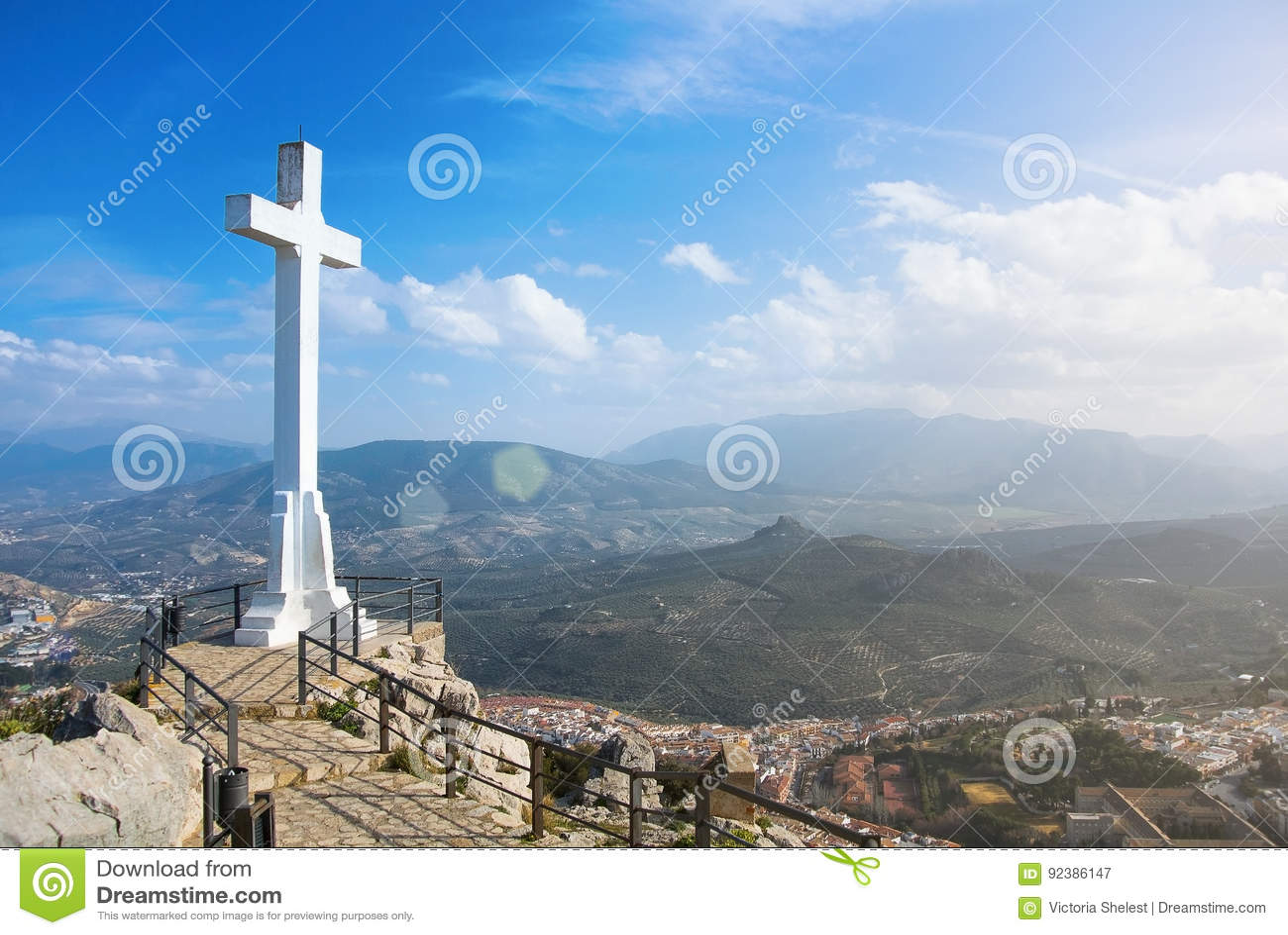 Белое пересекает сверх городок Jaen на гору, символ городка с горами Сьерры Magina на предпосылке на солнечный день