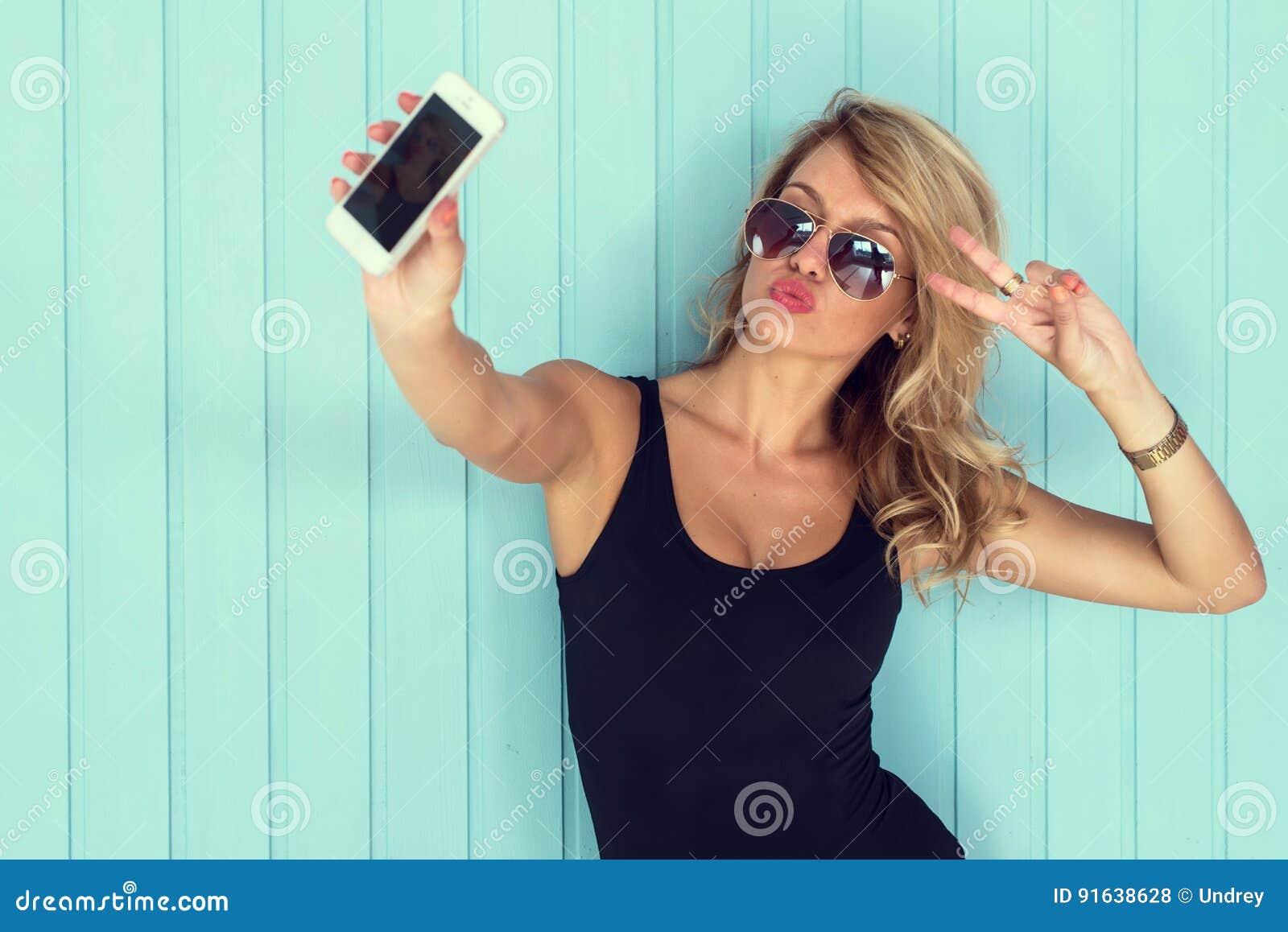 Белокурая женщина в bodysuit при совершенное тело принимая smartphone selfie тонизировала фильтр instagram