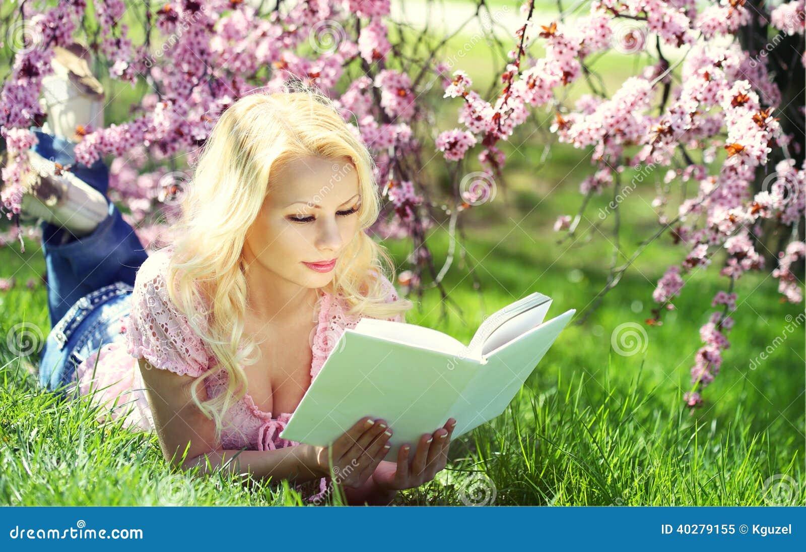 Белокурая женщина с книгой под вишневым цветом