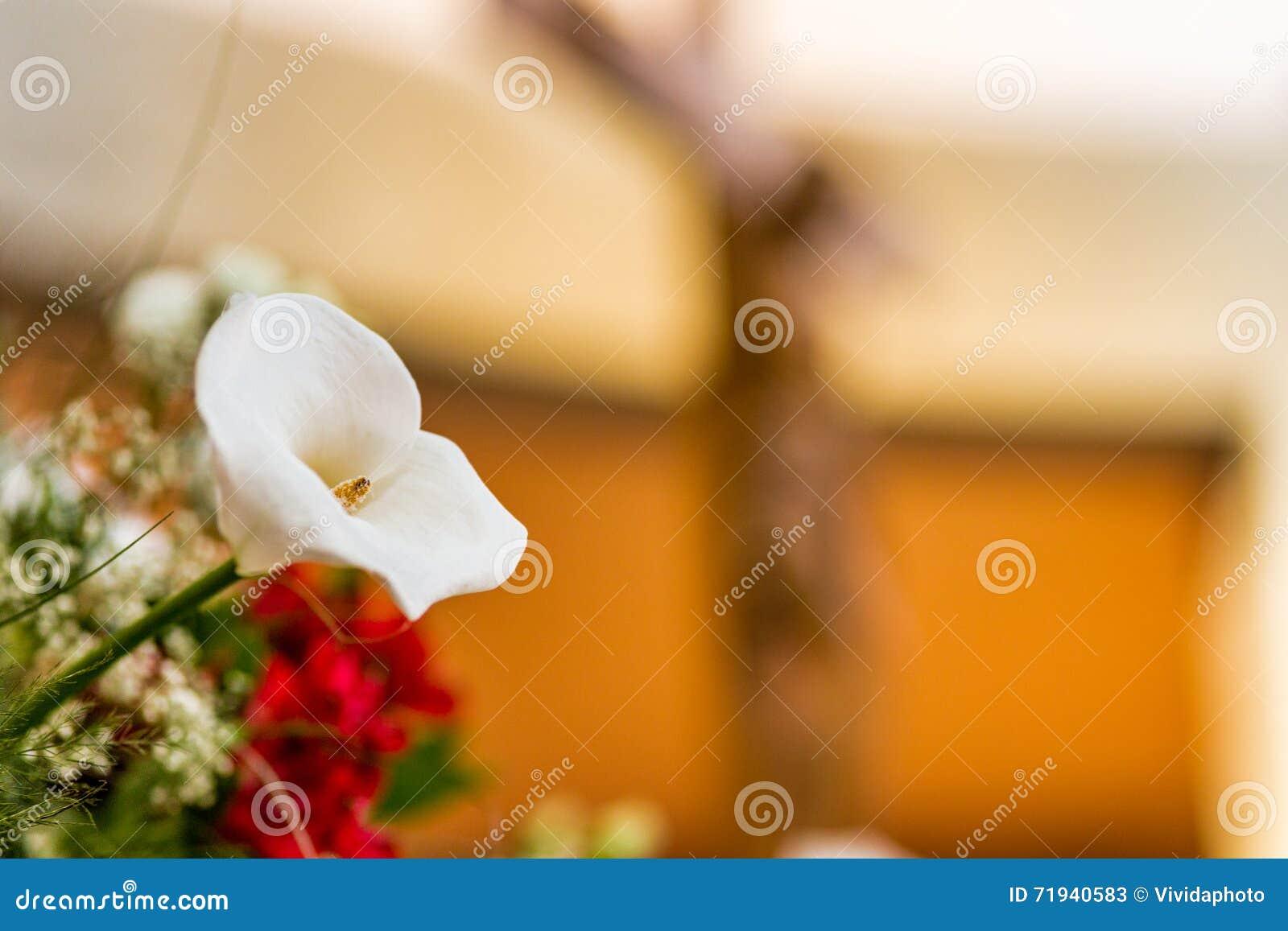 Белые лилия calla и распятие