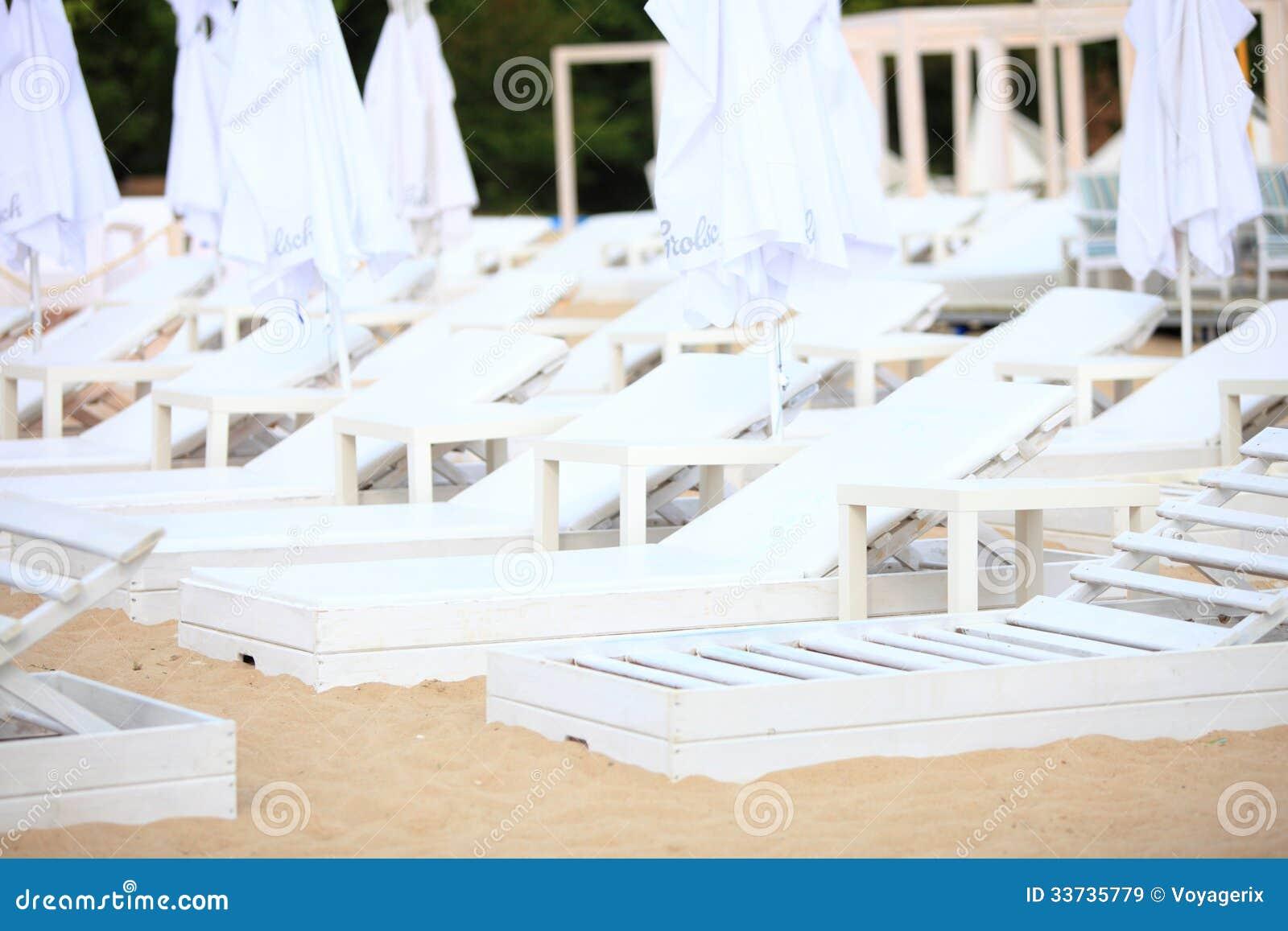 Белые стулья бассейна на пляже песка