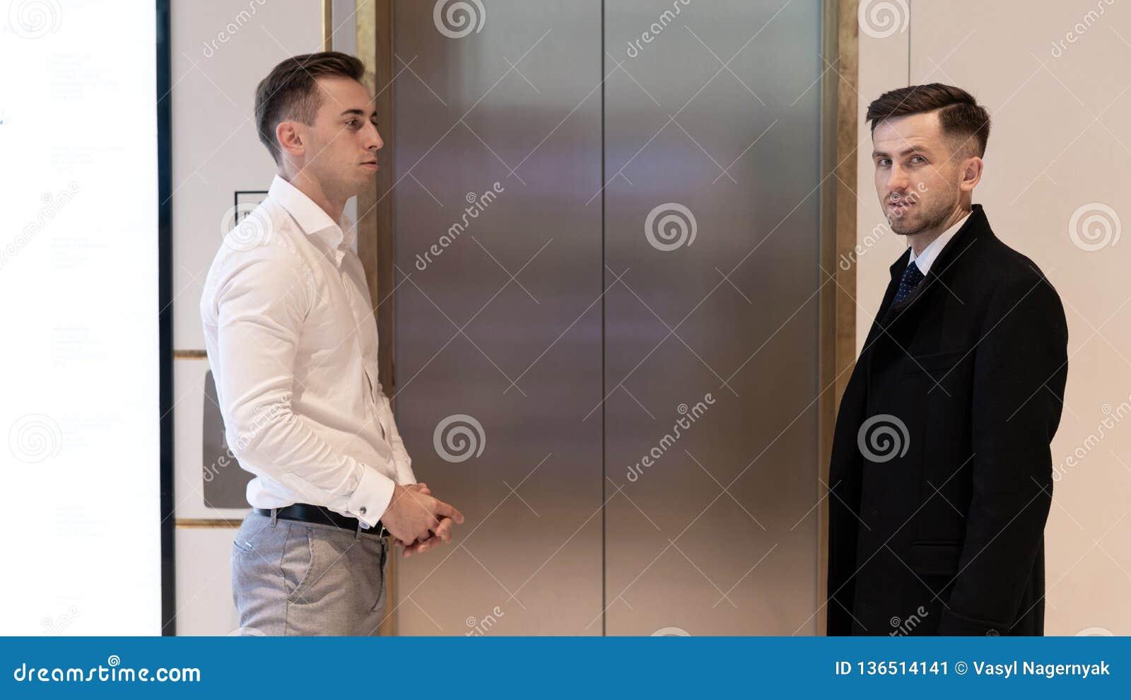 2 бизнесмена стоя около лифта Бизнесмены около лифта в офисе