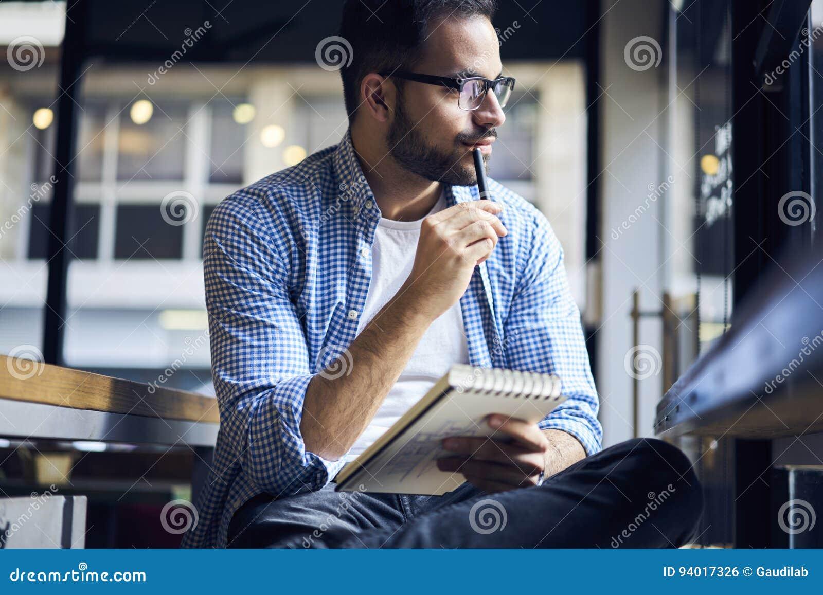 Бизнесмены в голубой рубашке создавая графические издержки для интерьера квартиры в тетради
