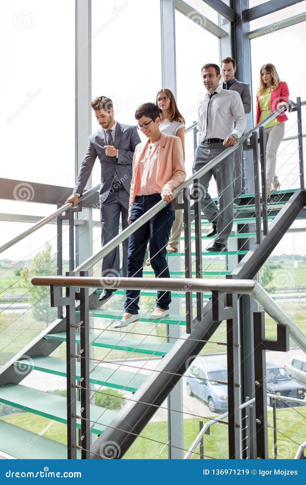 Бизнесмены идя вниз с лестниц