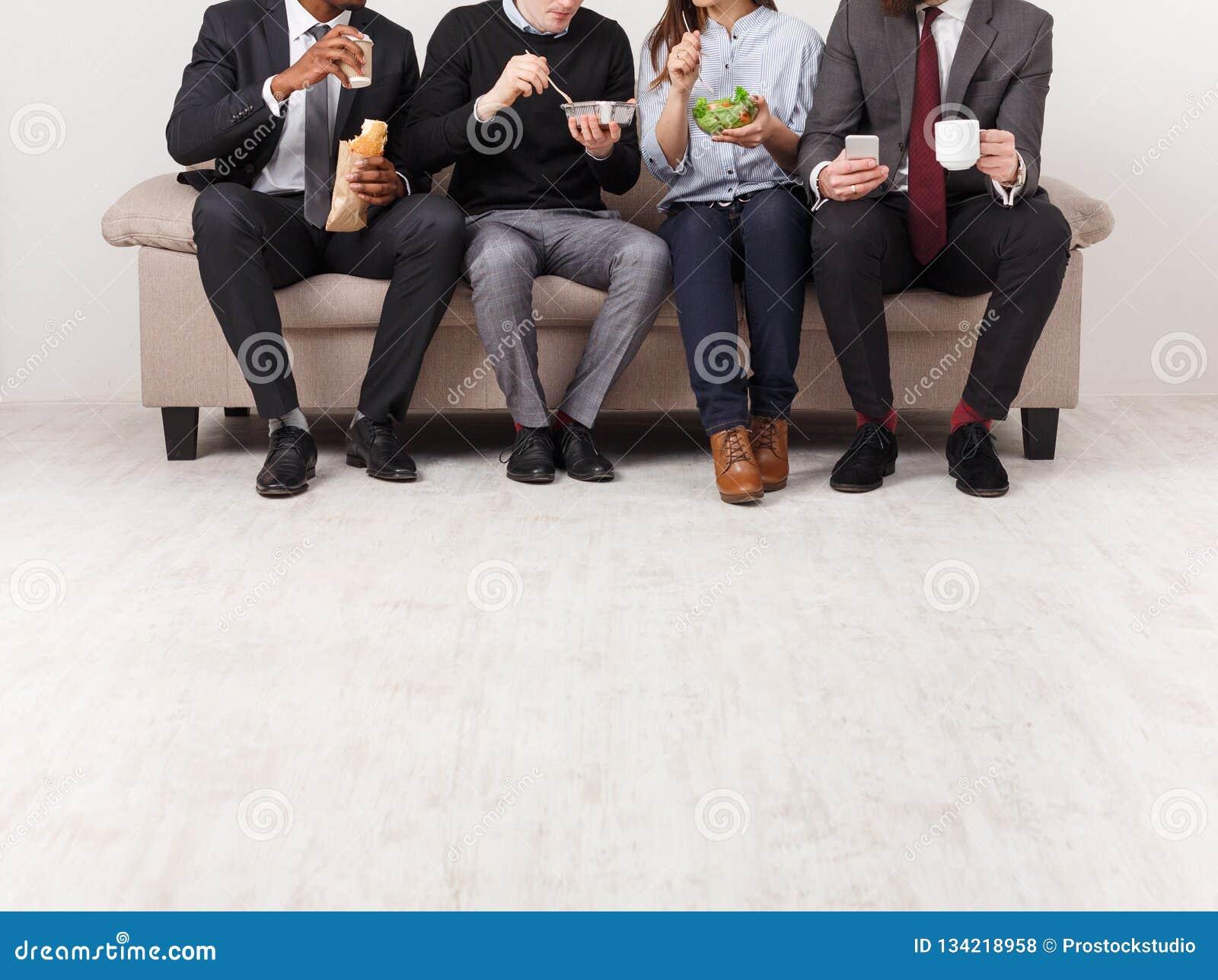 Бизнесмены имея обед в офисе