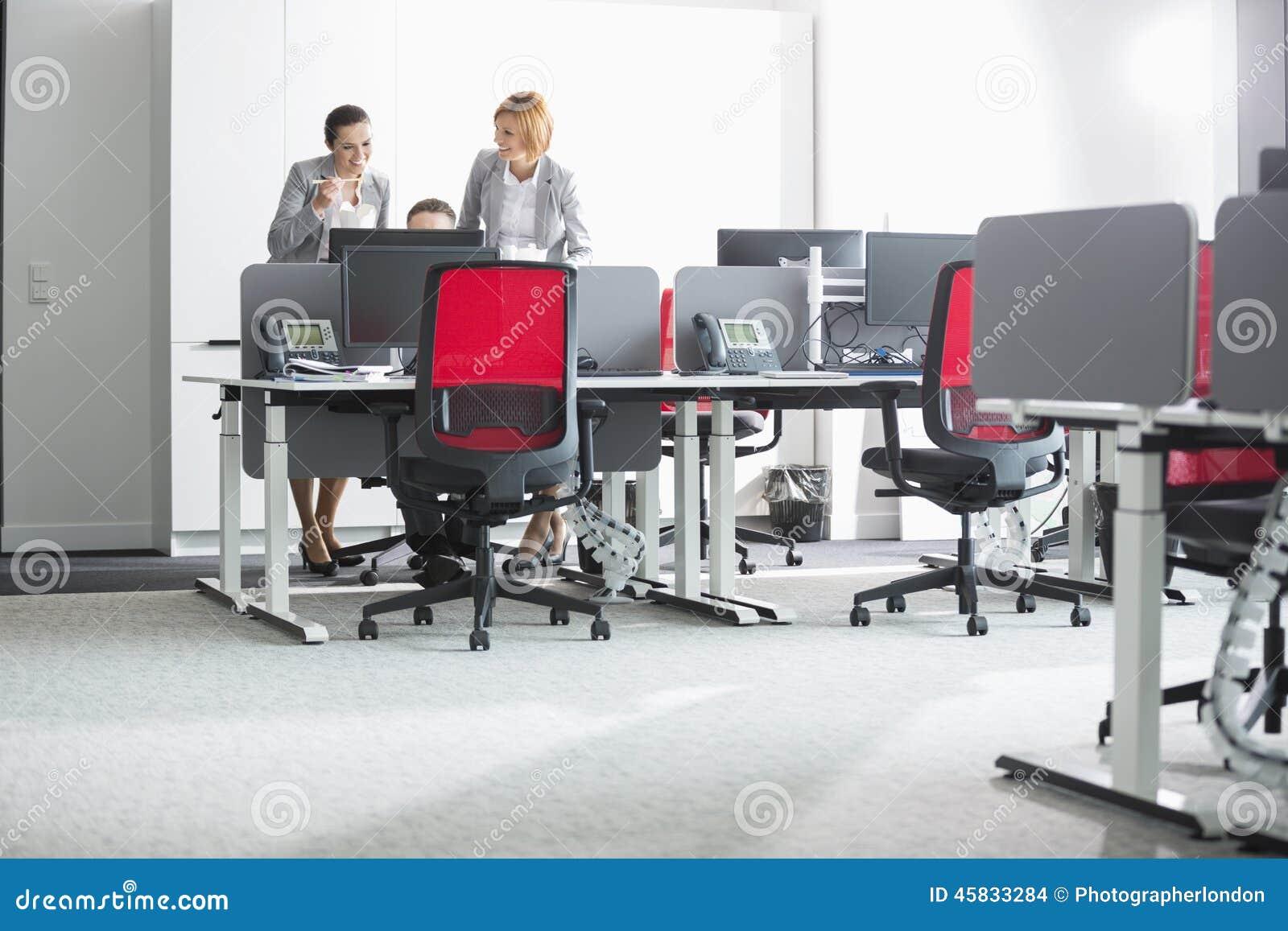 Бизнесмены имея обед пока использующ компьютер в офисе