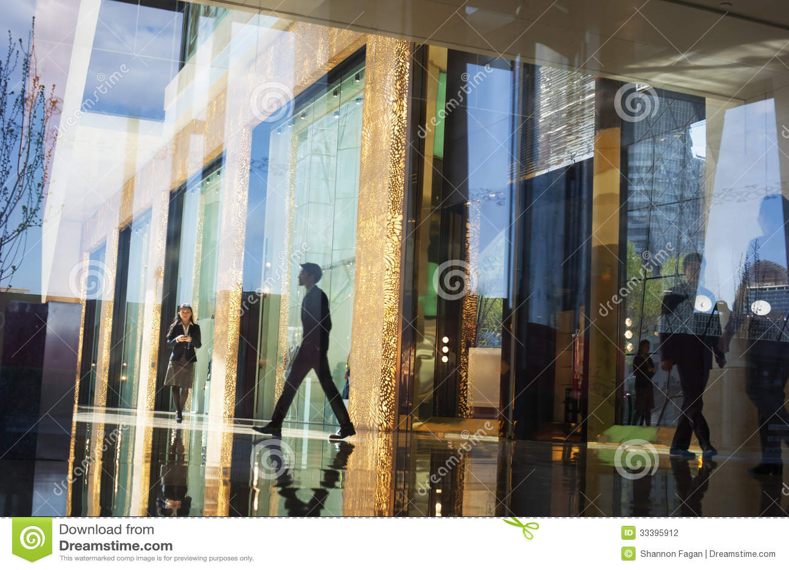 Бизнесмены идя через лобби офисного здания с другой стороны стеклянной стены