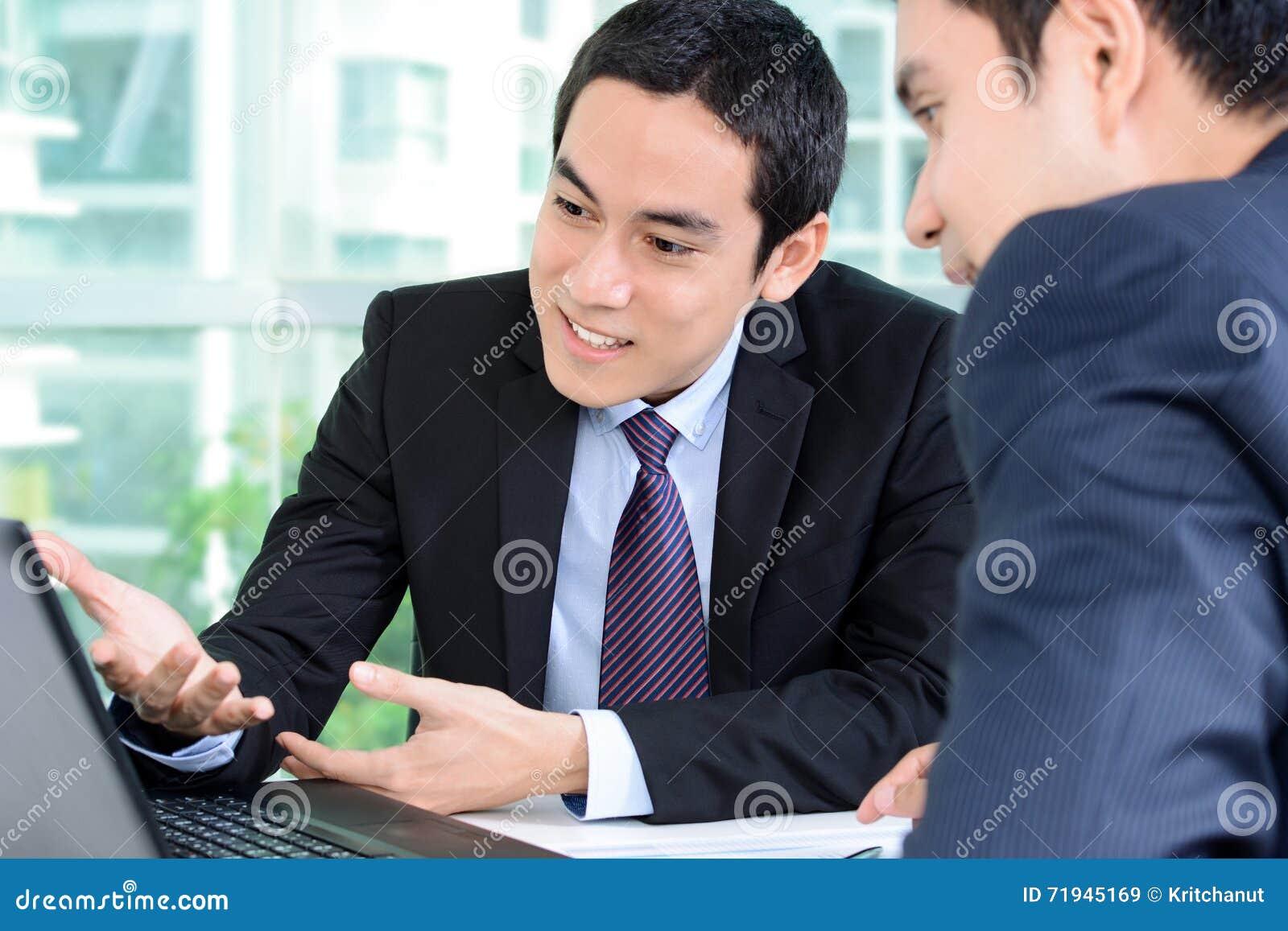 Бизнесмены обсуждая работу пока смотрящ портативный компьютер