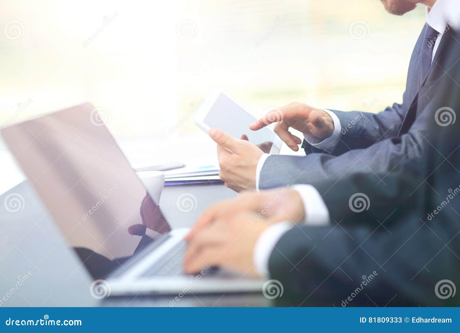 Бизнесмены работая с цифровыми таблеткой и компьтер-книжкой