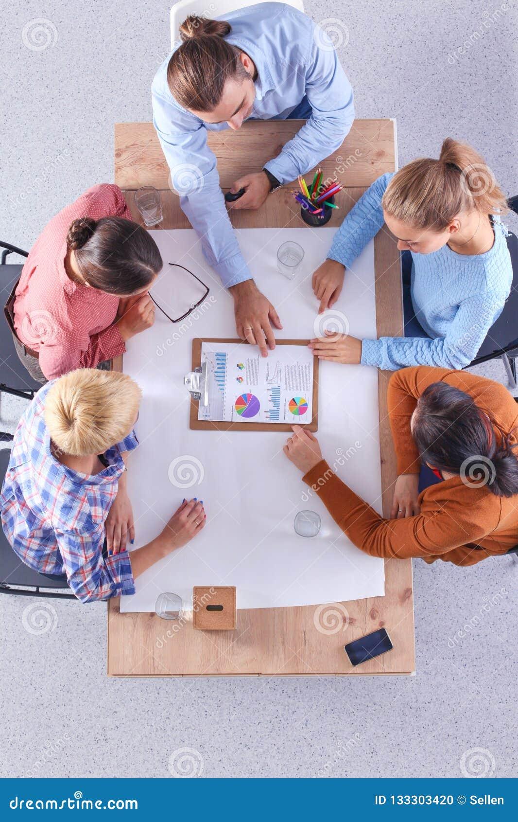 Бизнесмены сидя и обсуждая на встрече, в офисе