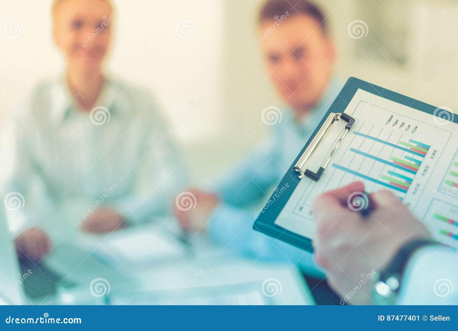 Бизнесмены сидя и обсуждая на деловой встрече, в офисе