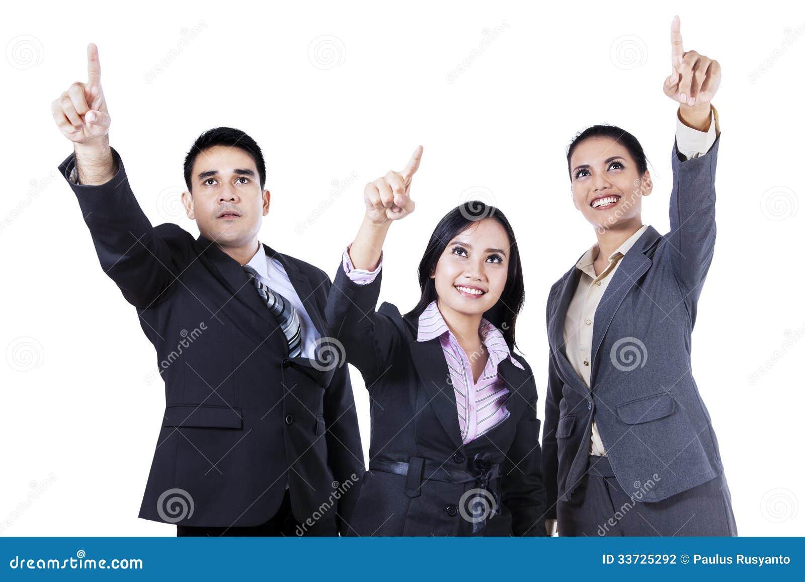 Бизнесмены стоя совместно указывающ и смотрящ вверх