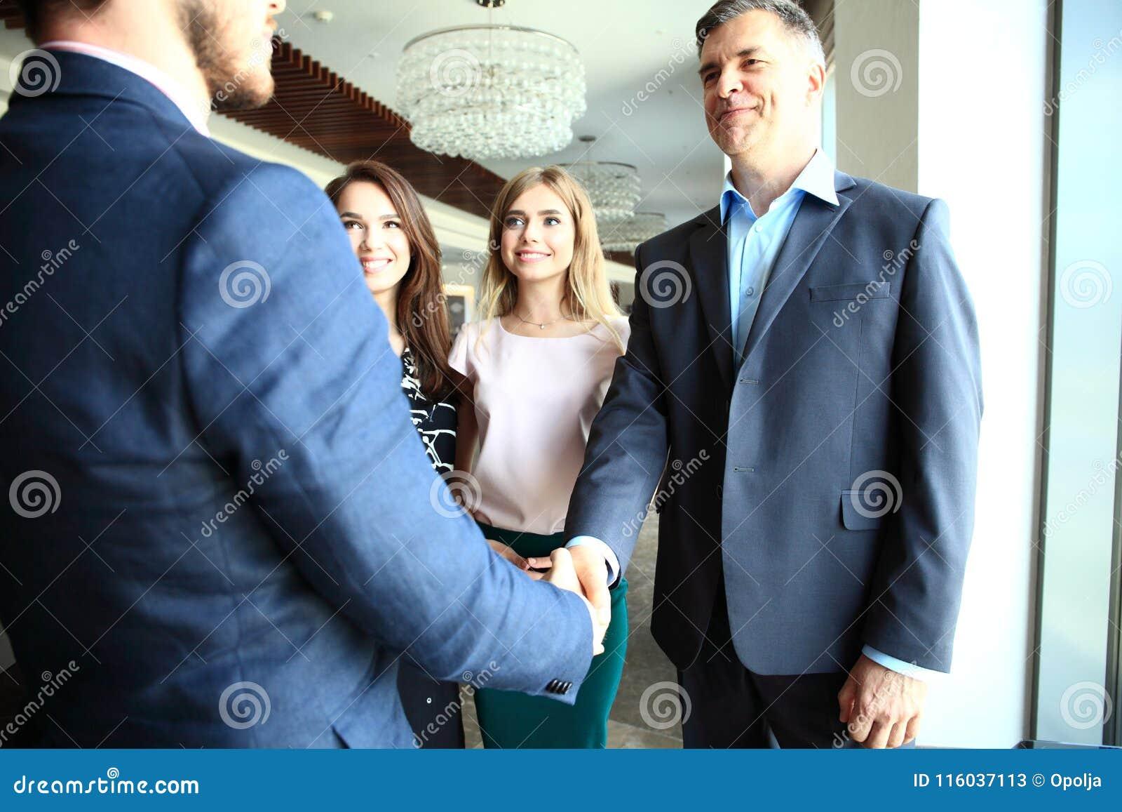 Бизнесмены тряся руки, заканчивая вверх встречу
