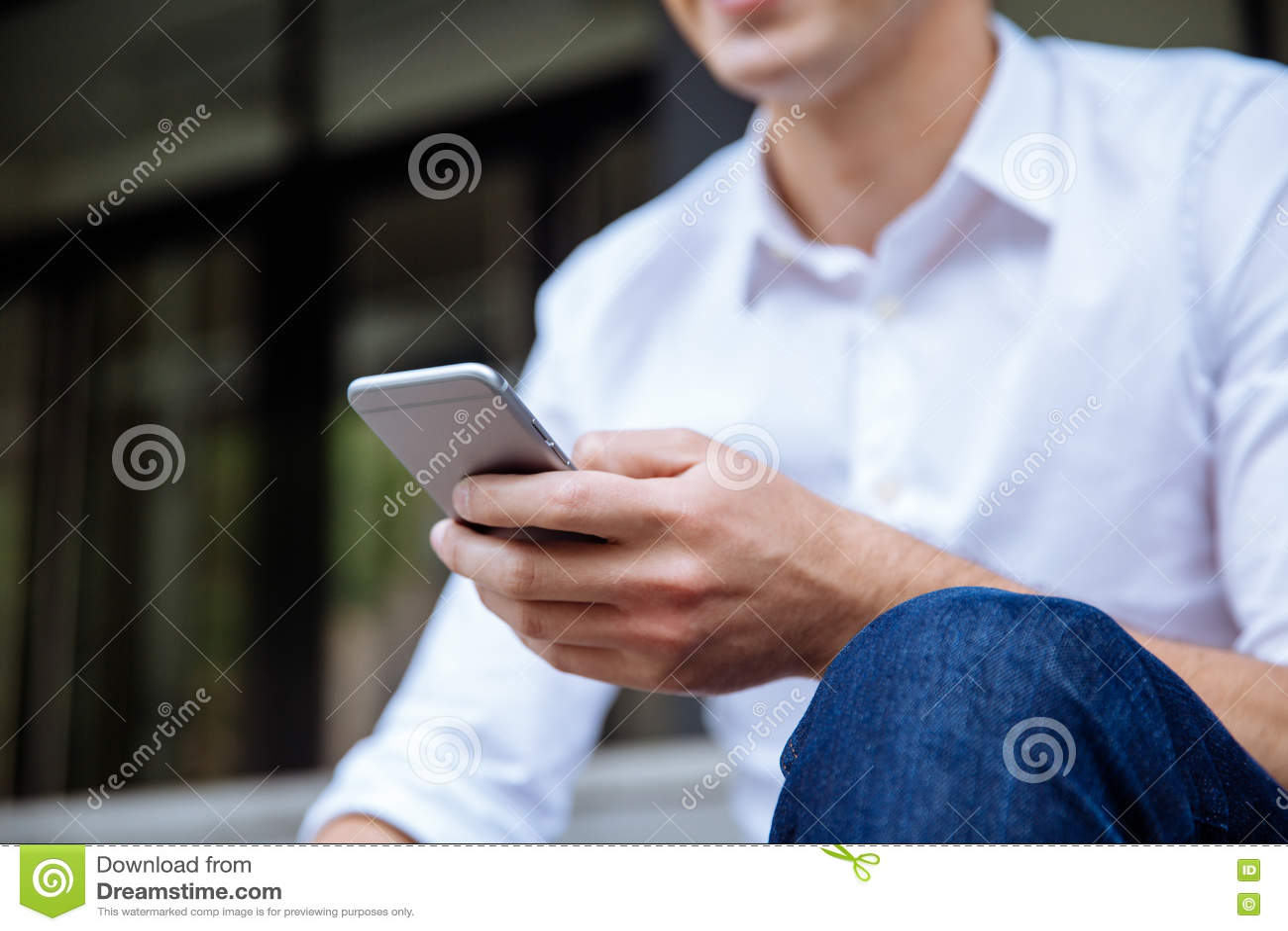 Бизнесмен в белых усаживании рубашки и использовать сотовом телефоне outdoors