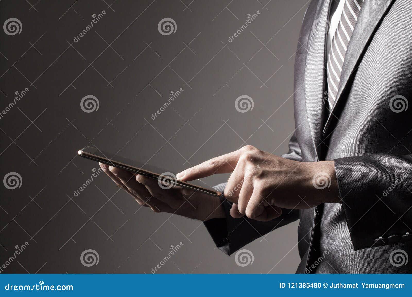 Бизнесмен в сером костюме держа таблетку касаясь социальной концепции технологии средств массовой информации