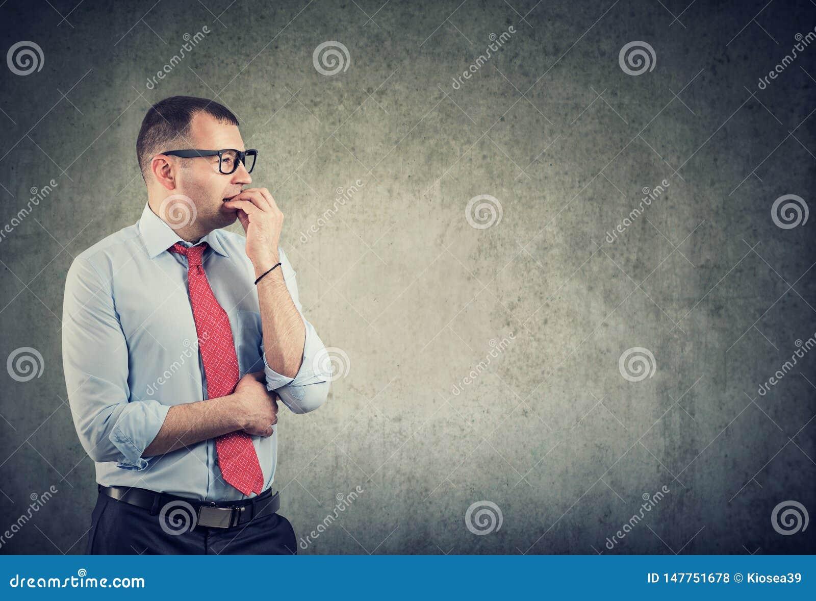 Бизнесмен в стеклах сдерживая ногти находясь в панике и тревожности смотря к стороне