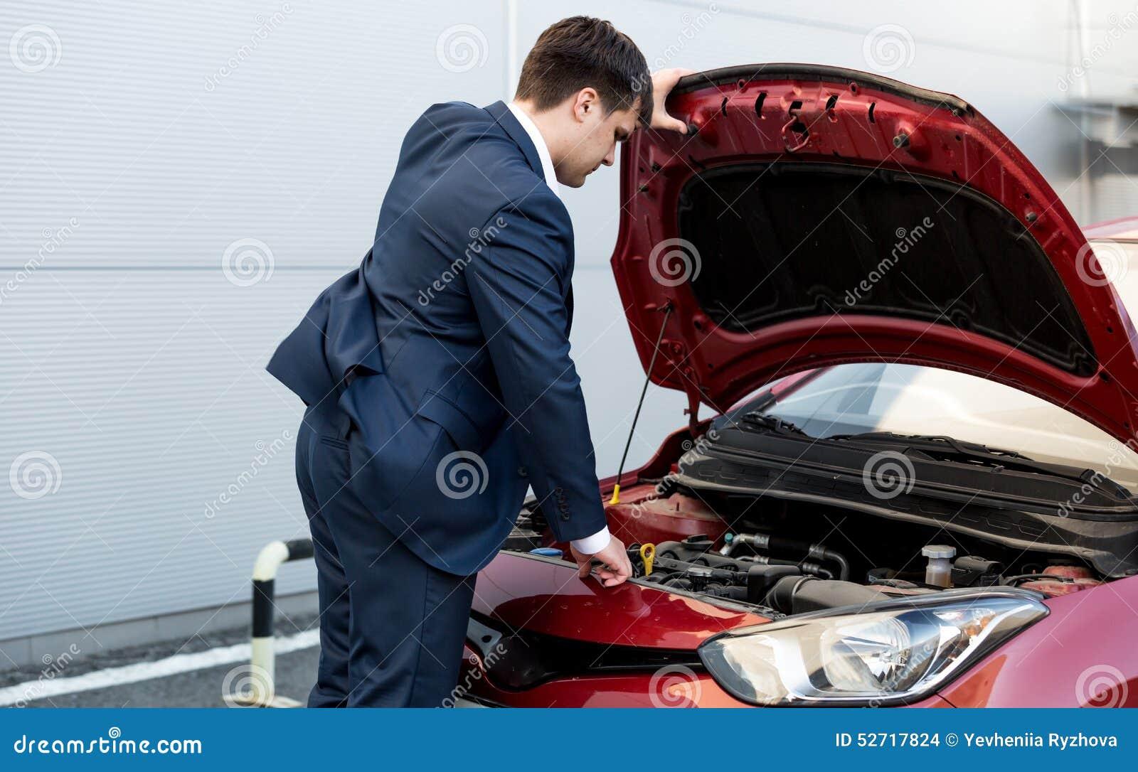 Бизнесмен в bonnet отверстия костюма открытого автомобиля