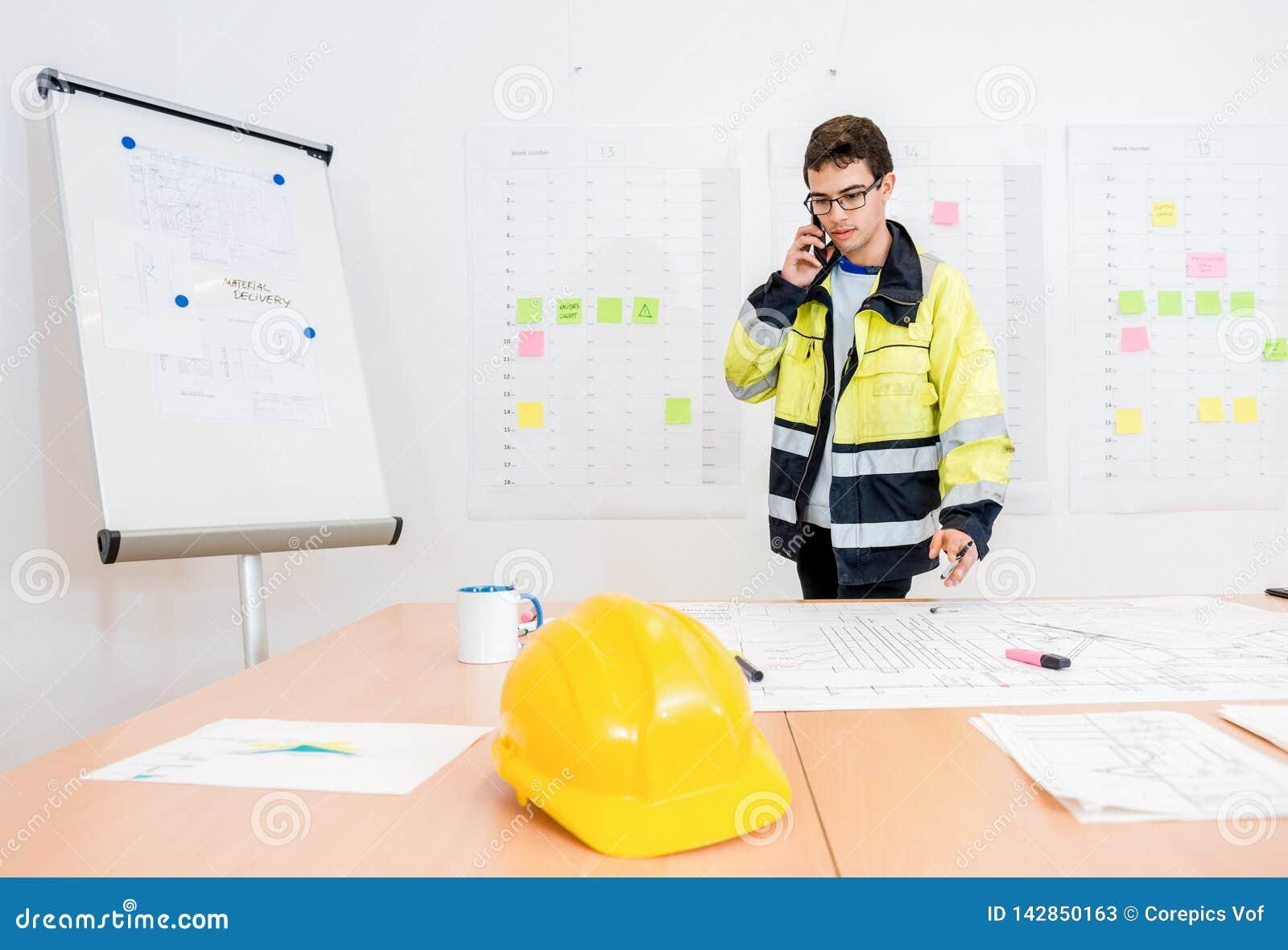 Бизнесмен говоря на мобильном телефоне на таблице офиса