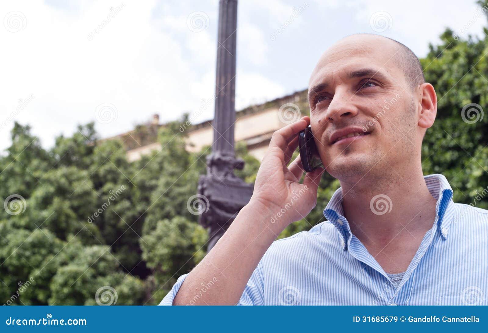 Бизнесмен говоря на мобильном телефоне outdoors