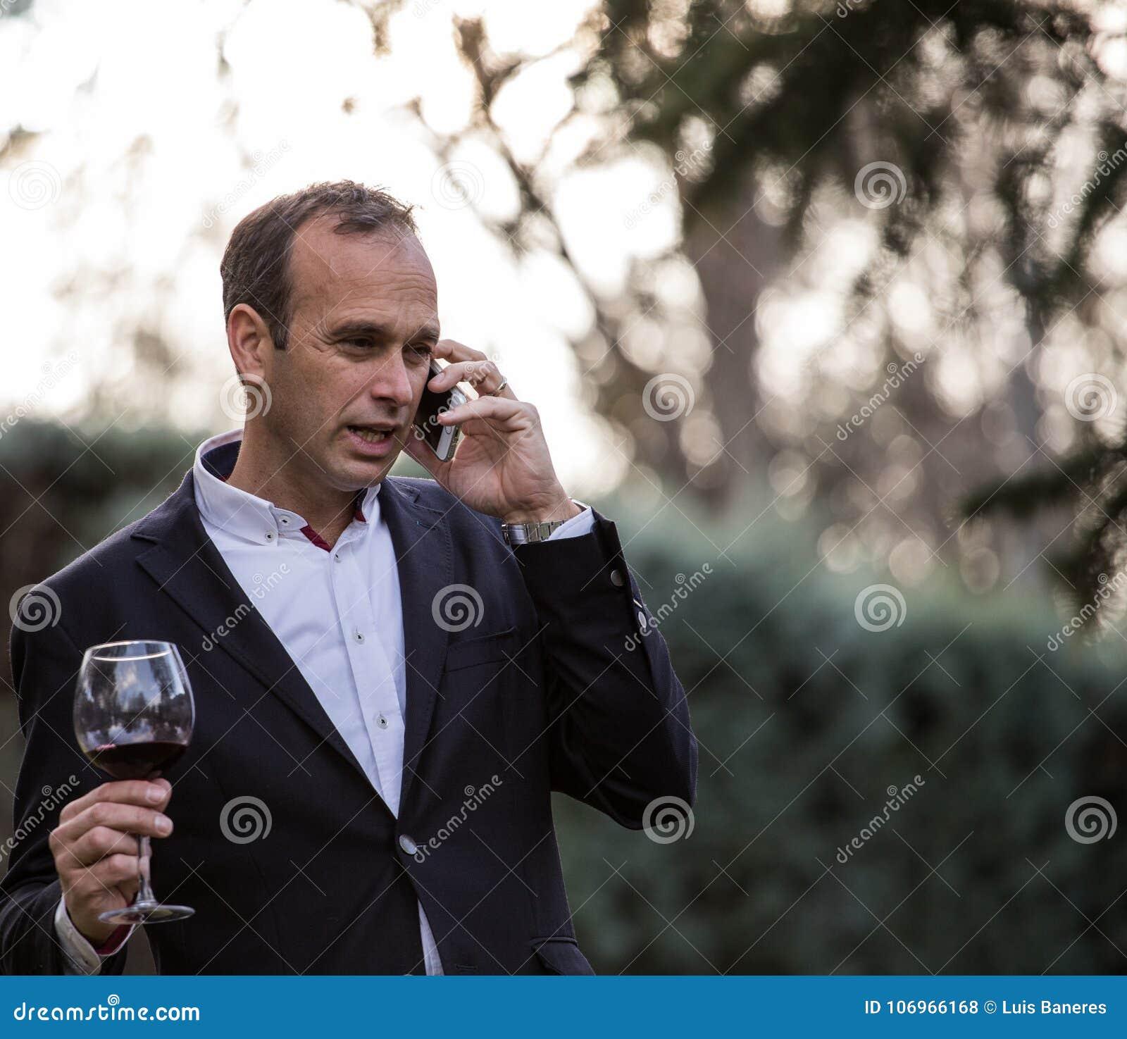 Бизнесмен говоря на телефоне и выпивая вине