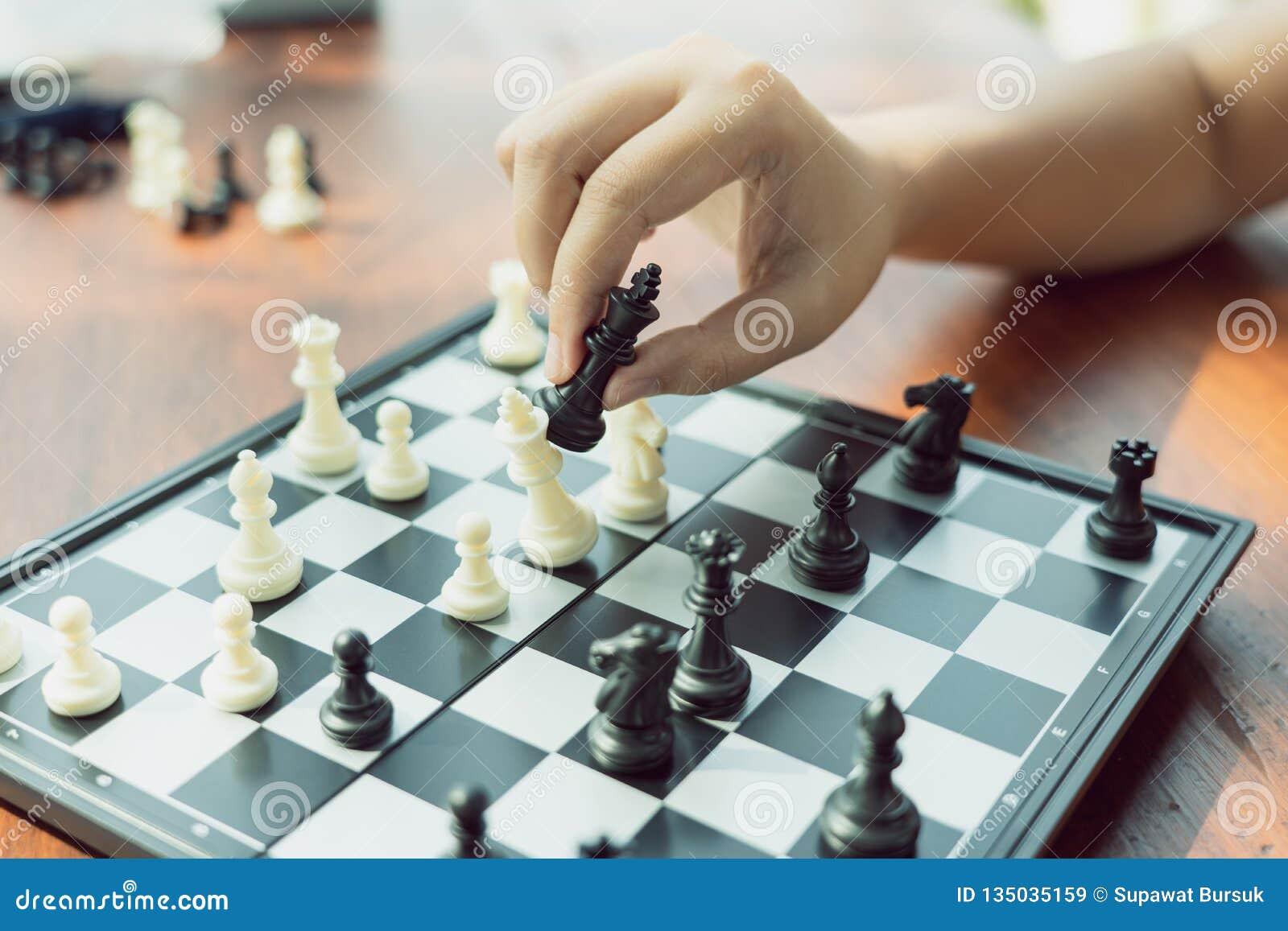 Бизнесмен держа короля Шахмат помещен на доске использование как концепция дела предпосылки и концепция стратегии с экземпляром