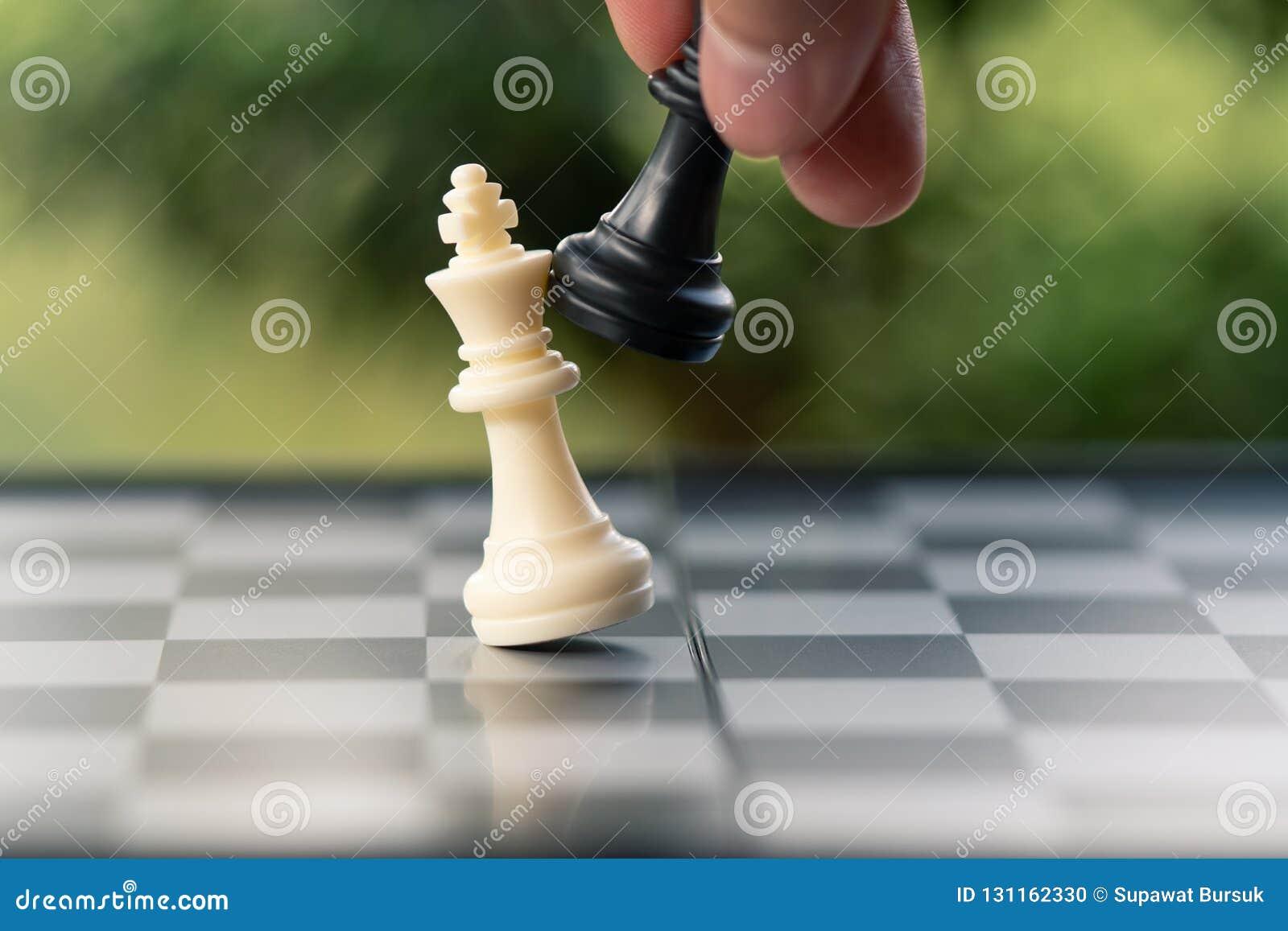 Бизнесмен держа короля Шахмат помещен на доске использование