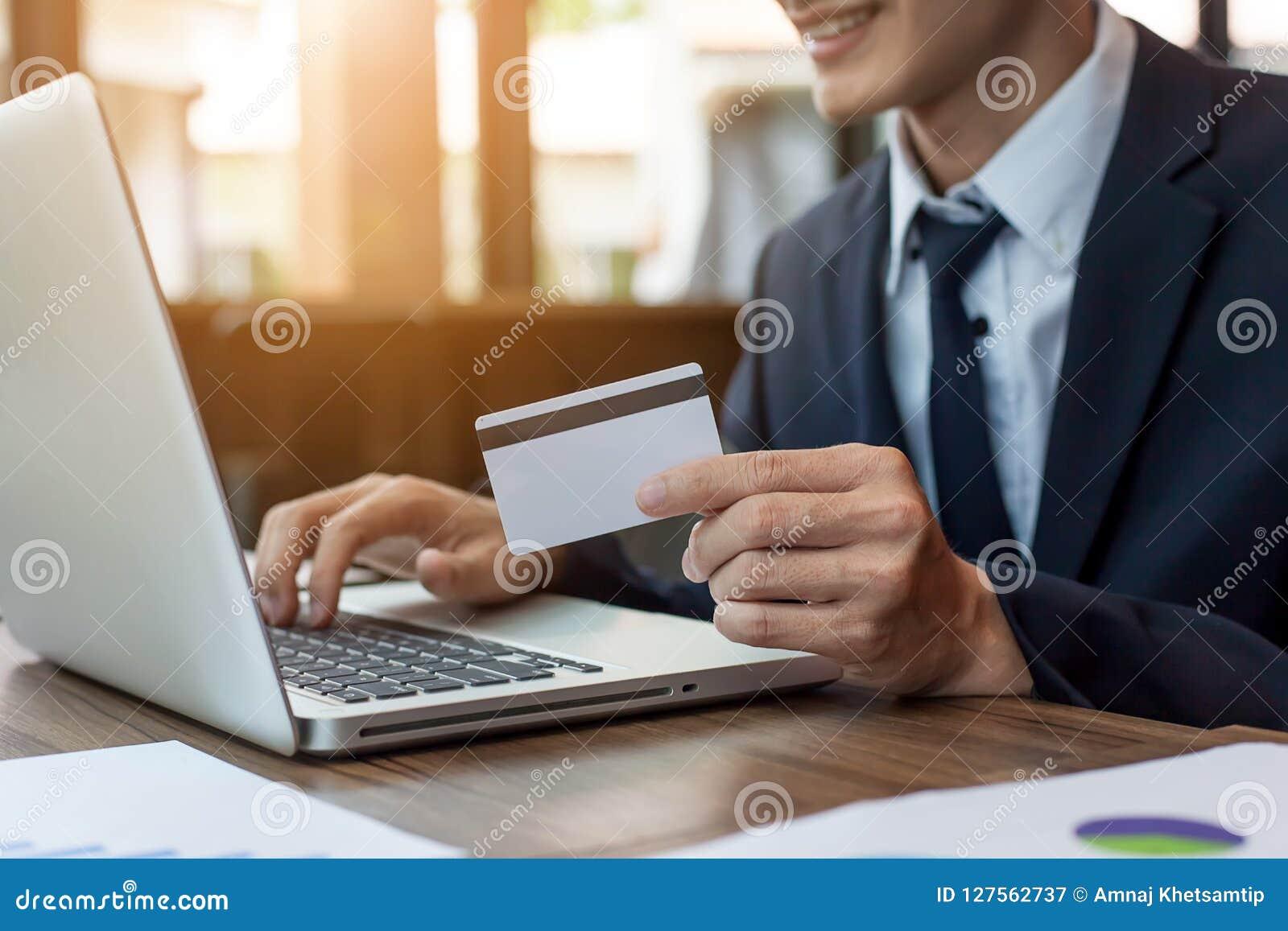Бизнесмен держа кредитную карточку и используя ноутбук