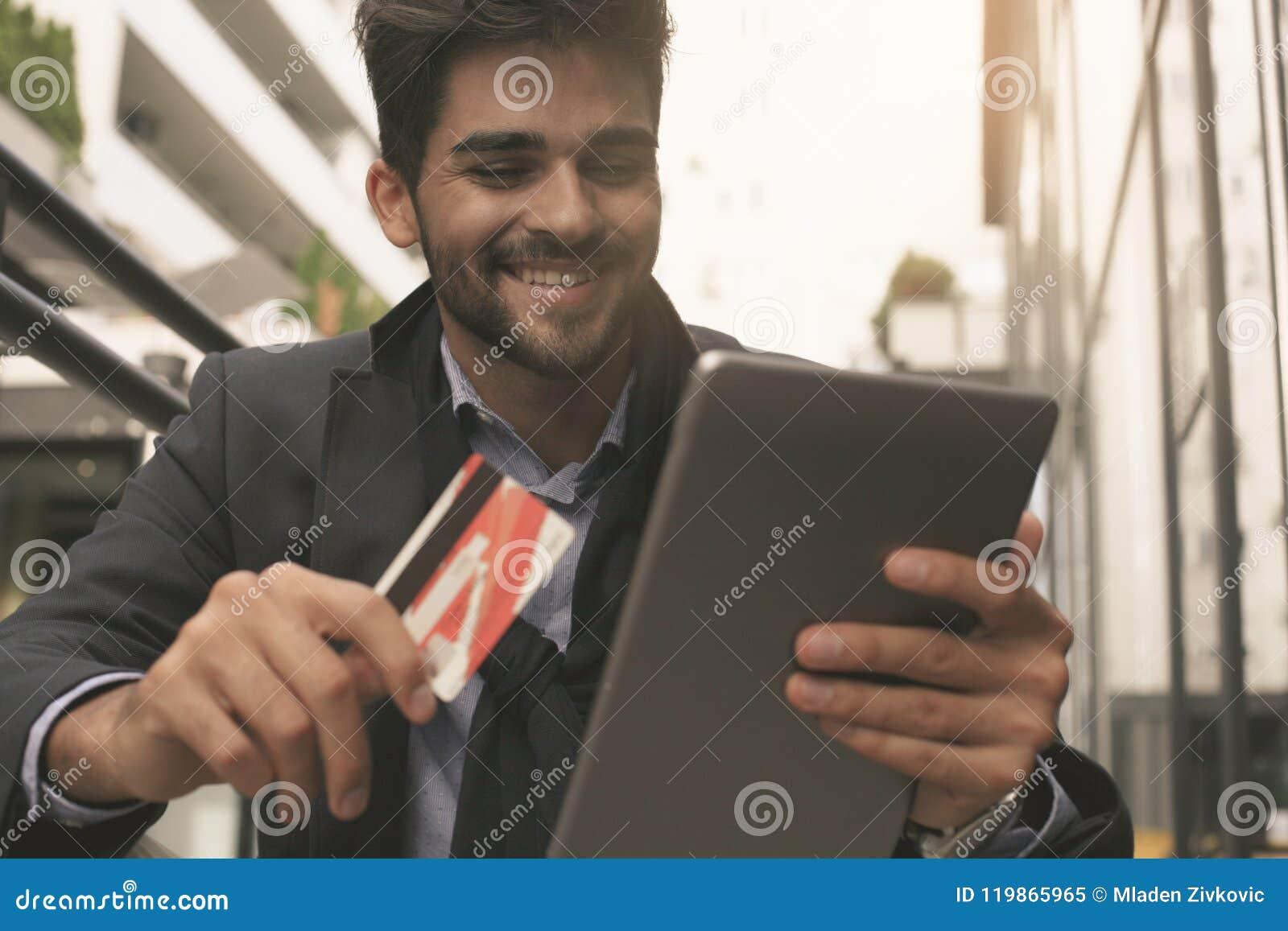 Бизнесмен держа кредитную карточку и цифровую таблетку