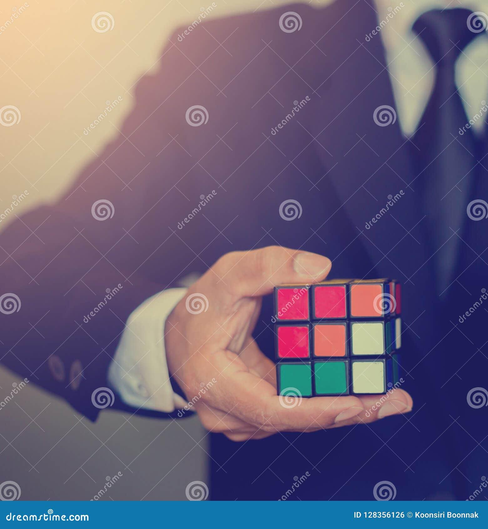 Бизнесмен держа куб Rubik